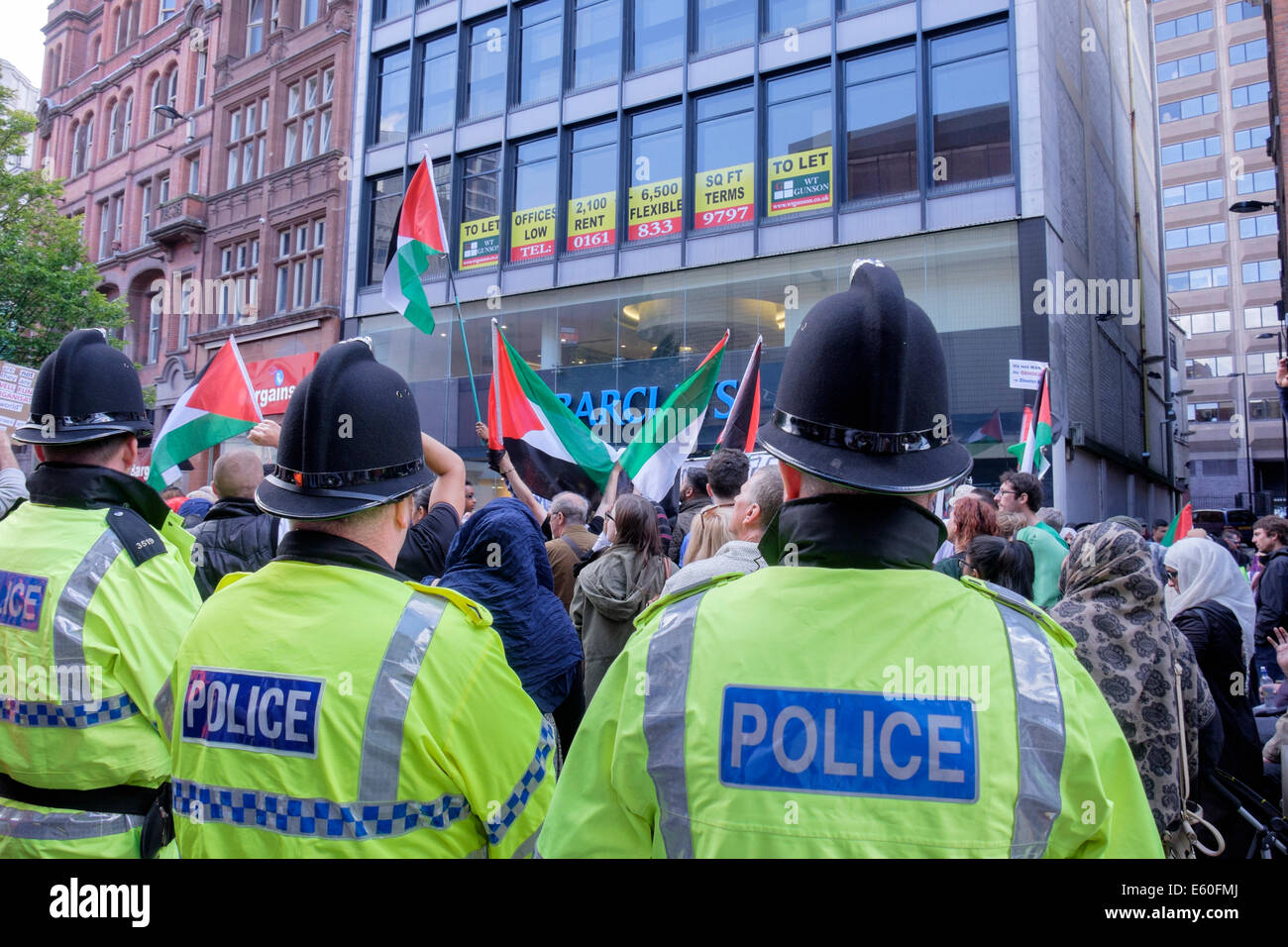 Manchester, UK. 9th August 2014. Police surround and observe the hundreds of demonstrators protesting outside Barclays - Stock Image