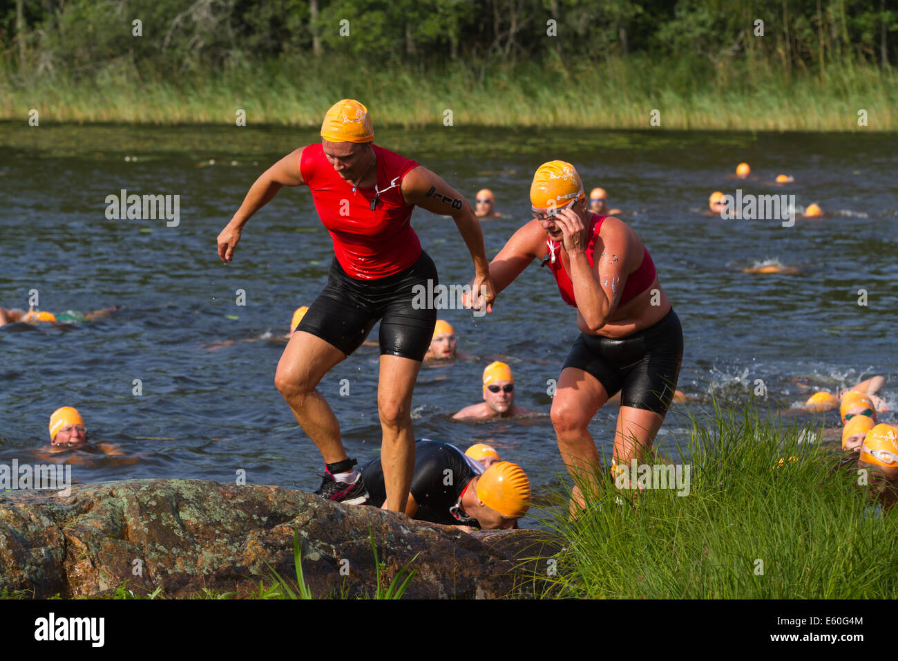 People competing in Ångaloppet, a swimrun competition where you run on land and swim in lakes and the sea several - Stock Image