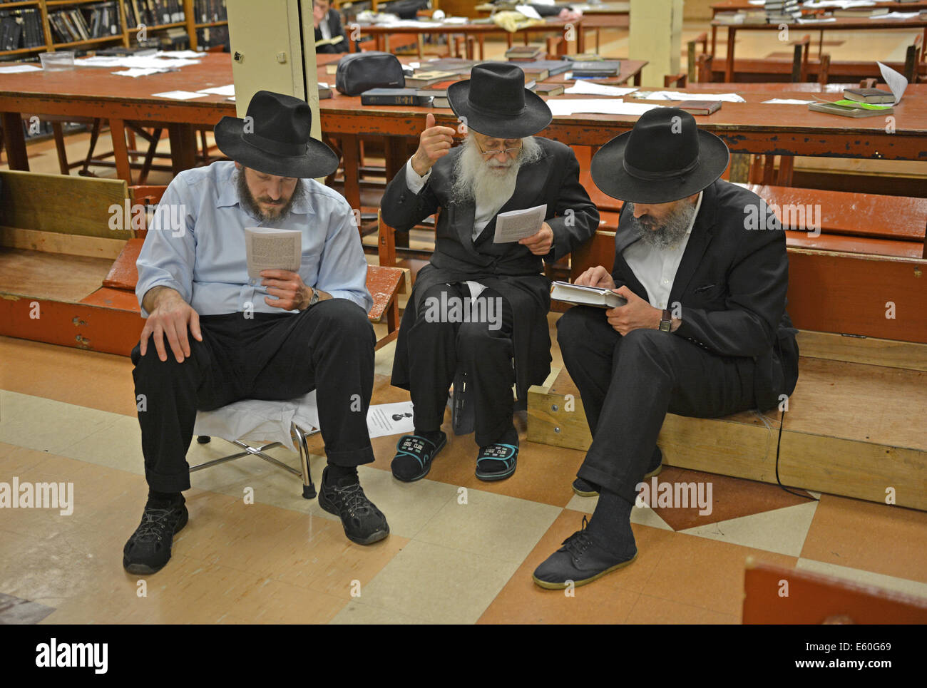 Religious Jewish men studying during Tisha B'Av morning services in a synagogue in Brooklyn, New York - Stock Image