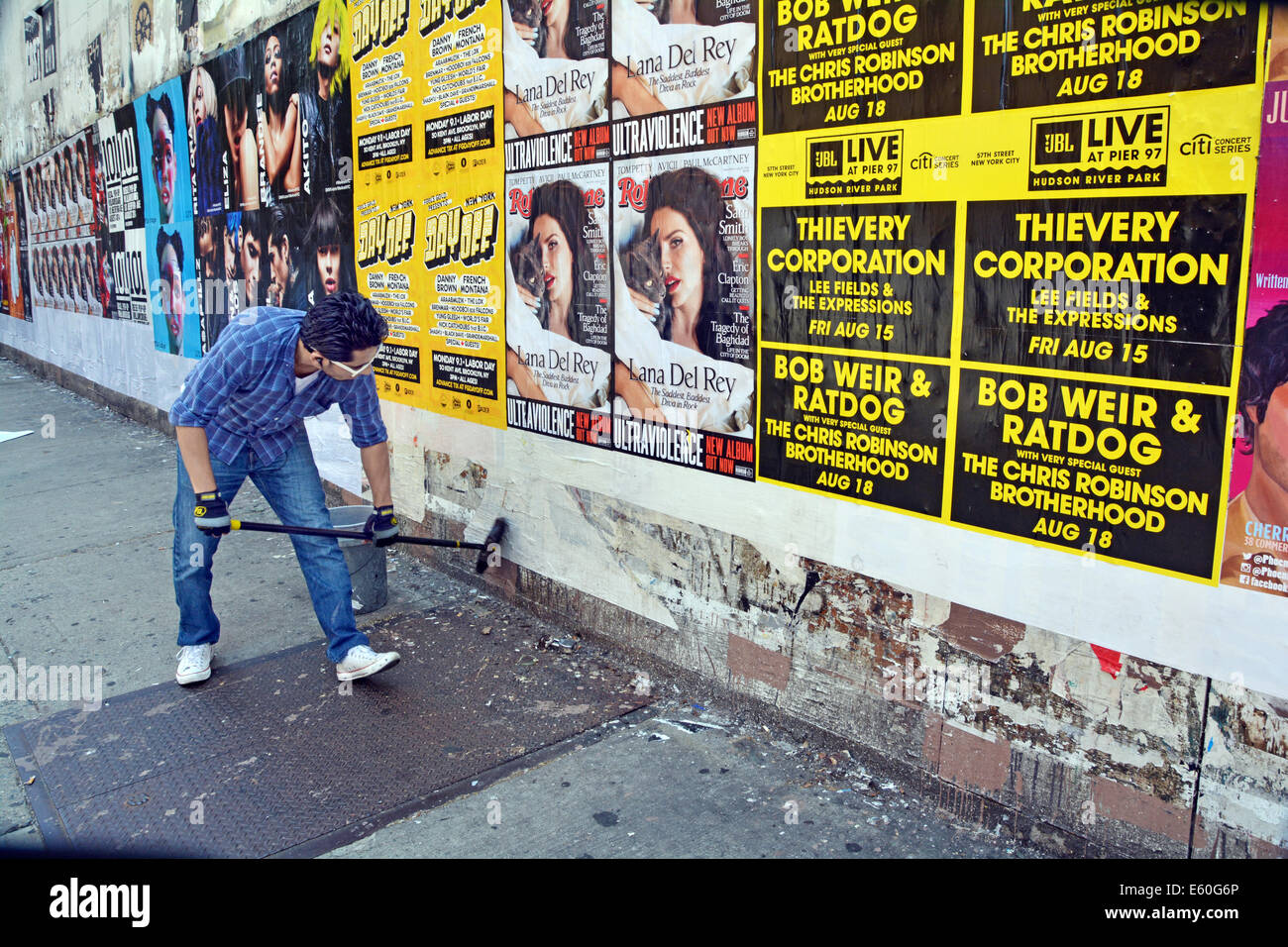 A man with the unusual occupation of hanging posters for rock shows. In Greenwich Village, New York City - Stock Image