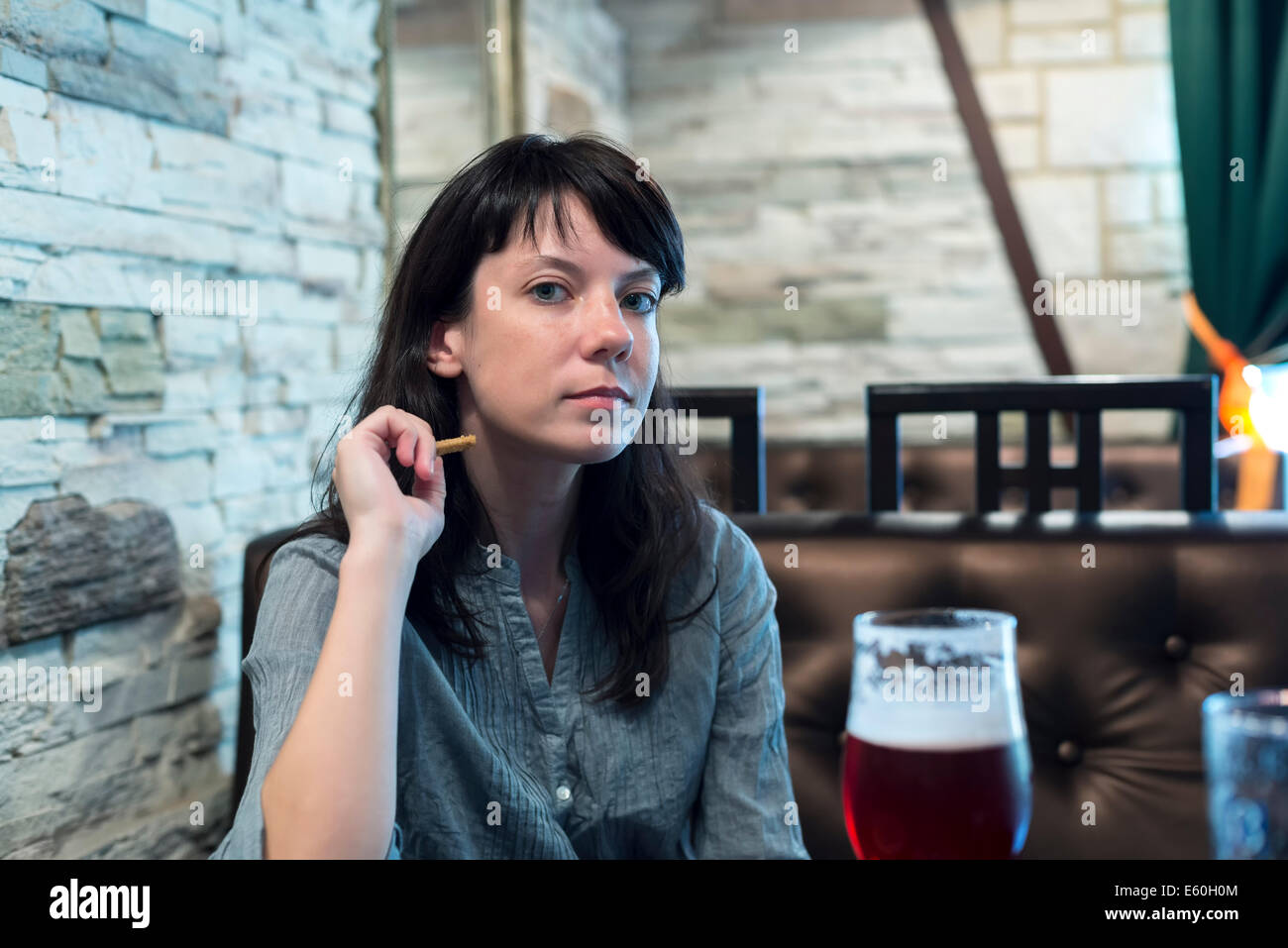 girl sitting at the bar with a glass of cherry beer - Stock Image