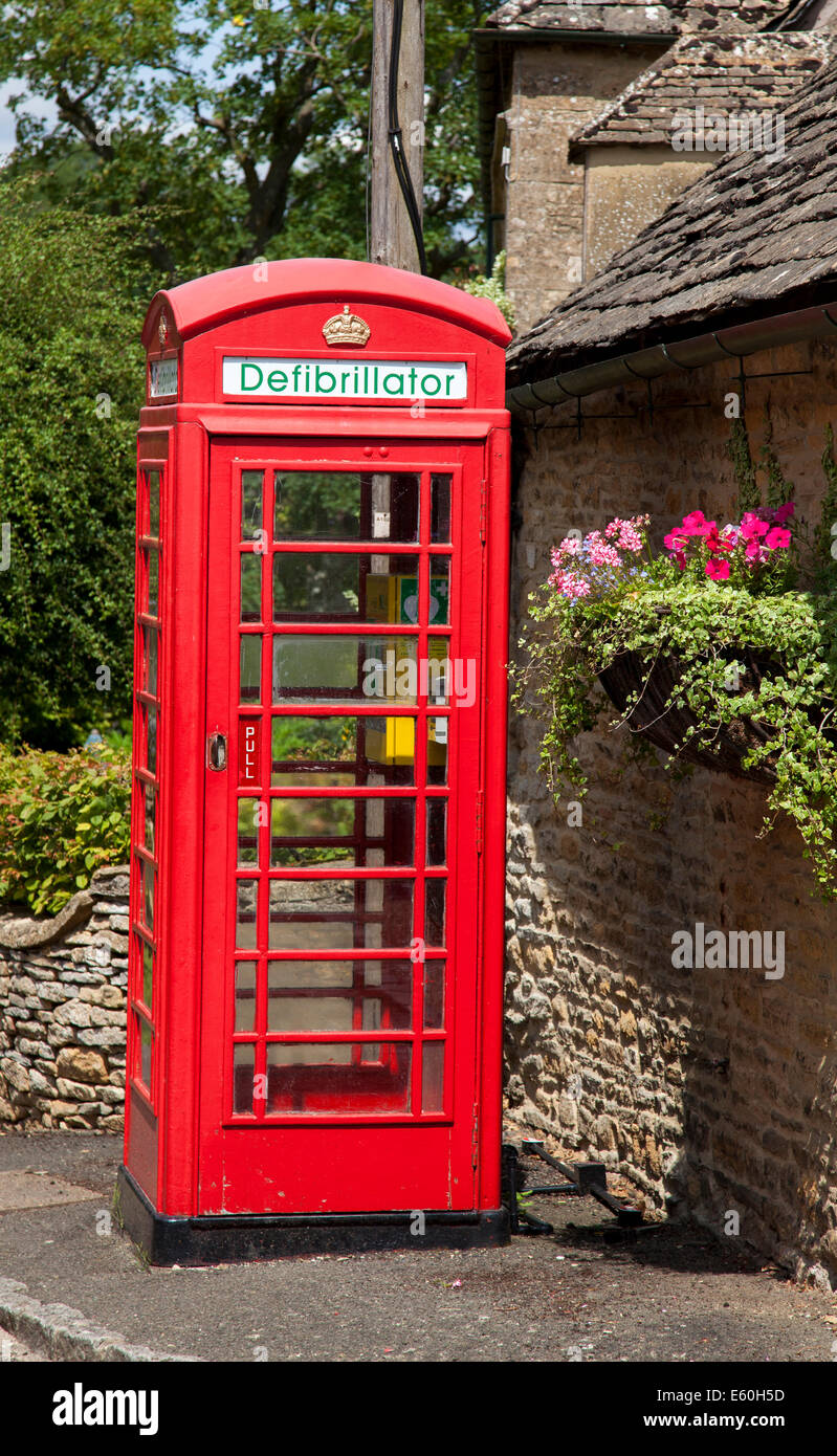 A defibrillator in a red telephone box in the village of Upper Slaughter, The Cotswolds, Gloucestershire, England, - Stock Image