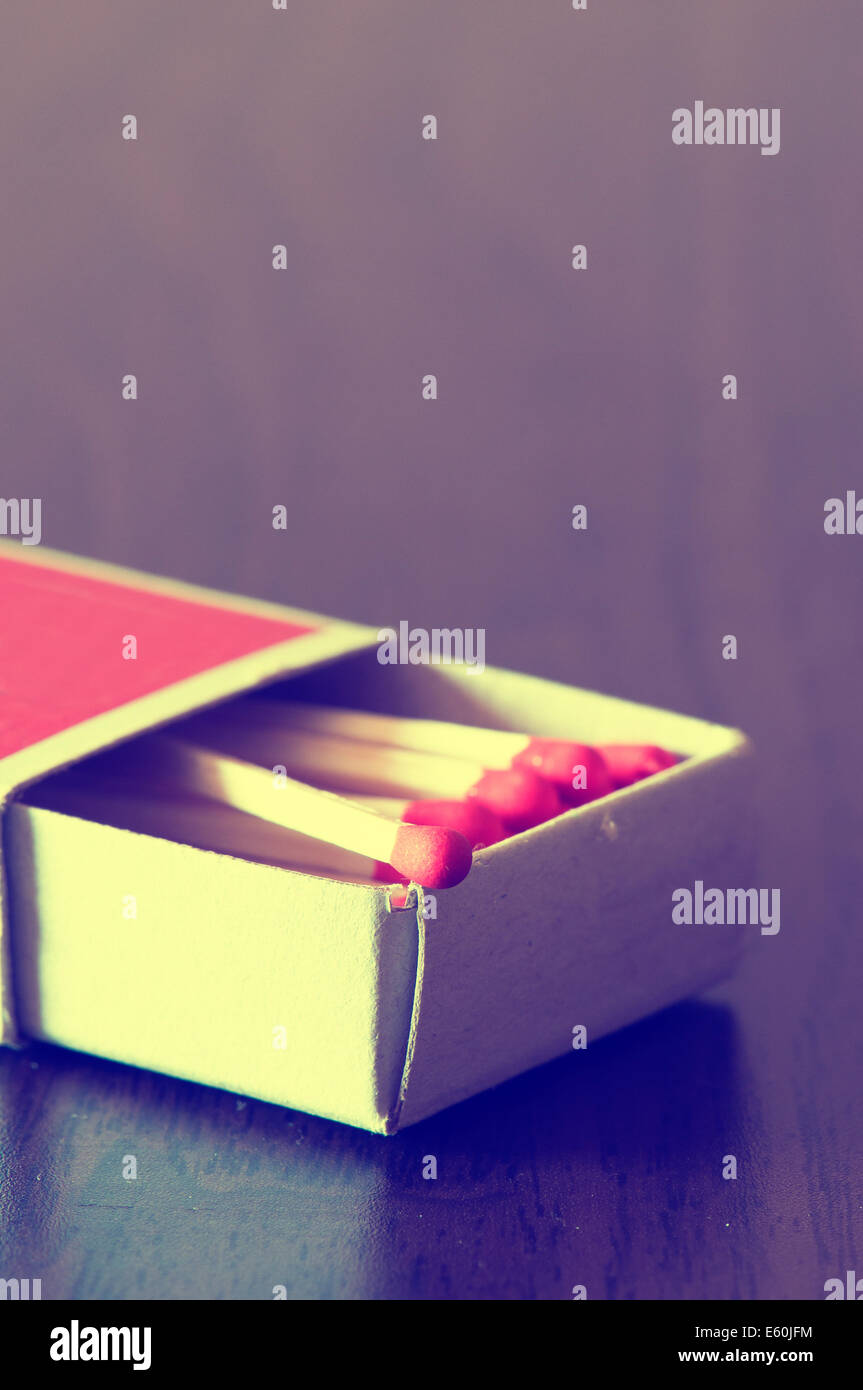 matchbox full of red matches on table - Stock Image