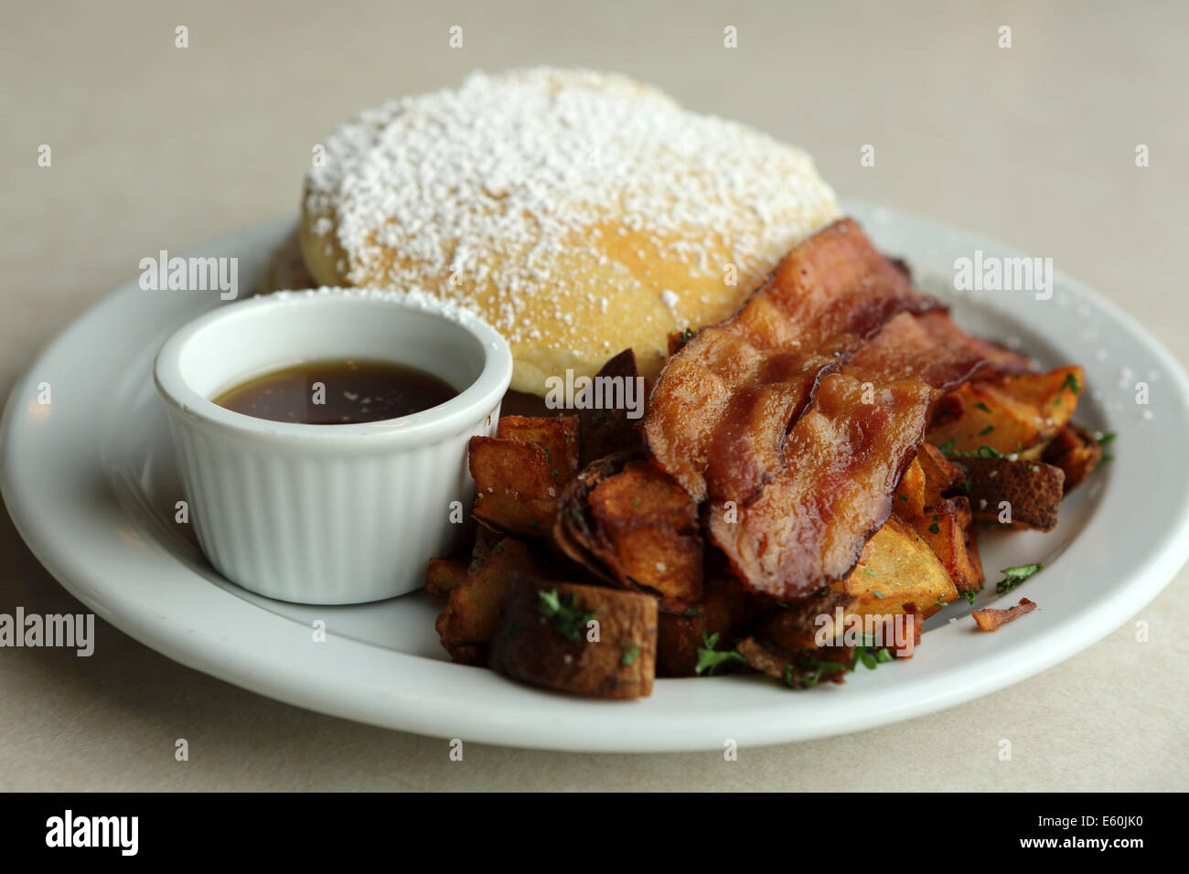 A breakfast of pancakes, crispy bacon, potatoes and maple syrup served in Saskatchewan, Canada. - Stock Image
