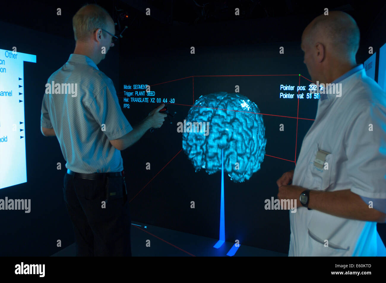 Technician helping a medical specialist with a virtual brain research calibration who is doing research on Alzheimers - Stock Image