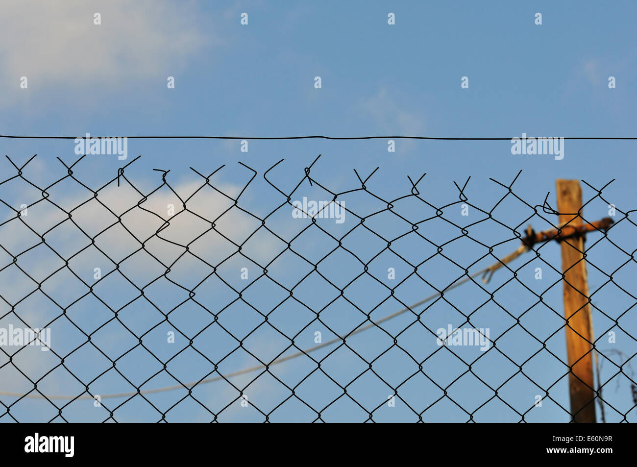 Chain link fence and blue sky urban background. - Stock Image