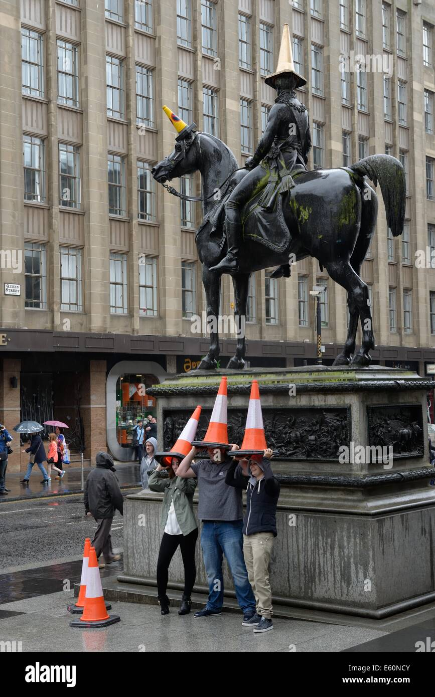 The Wellington statue in Glasgow , Scotland, adorned with traffic cone with tourists copying and taking pictures. - Stock Image
