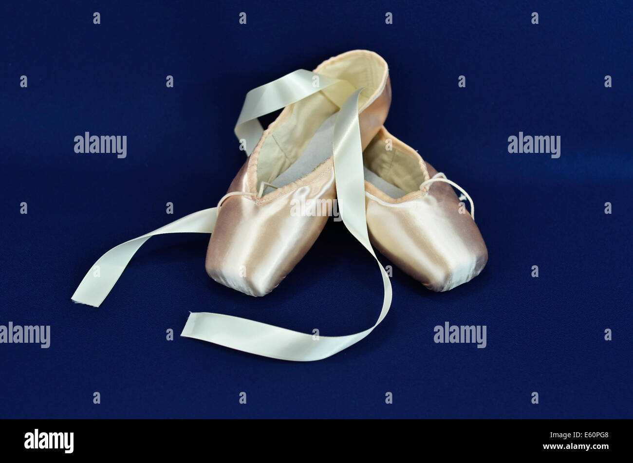 Ballet shoes on blue background - Stock Image
