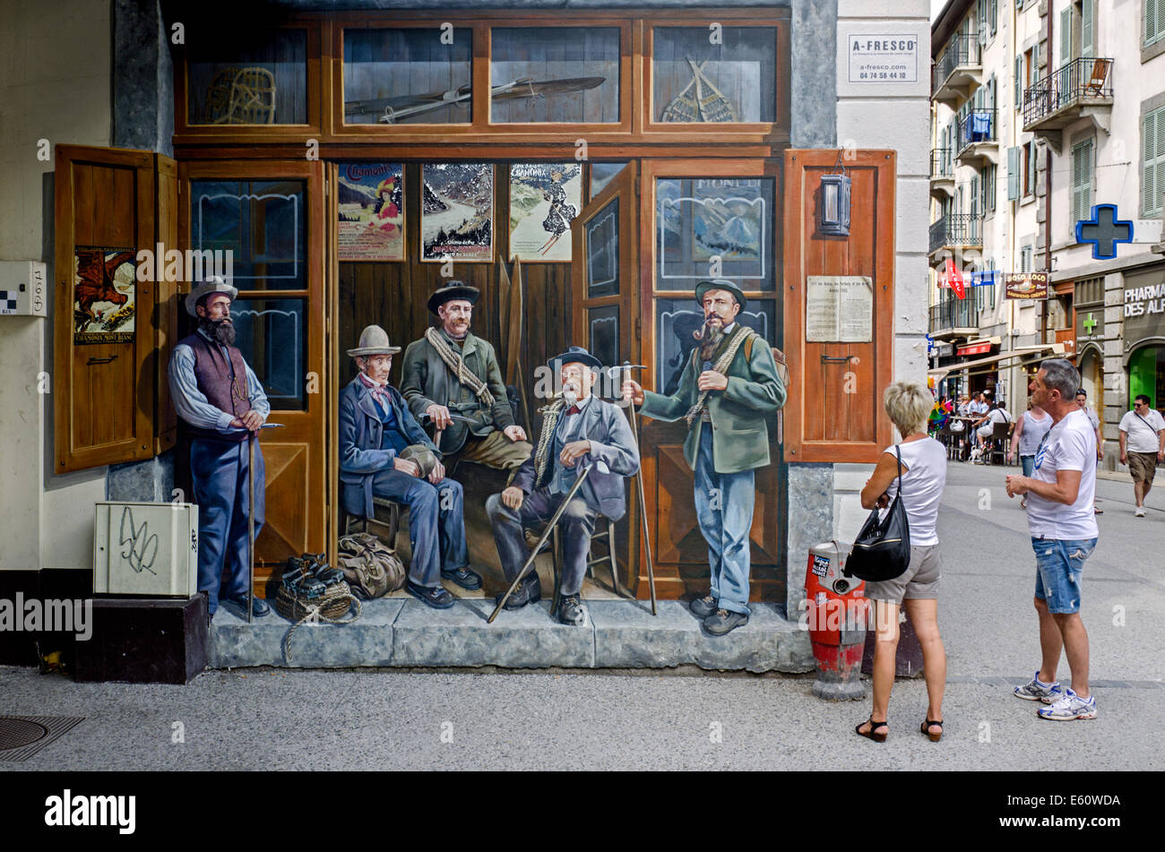 Tourists study the Compagnie des Guides mural in the French town of Chamonix. - Stock Image