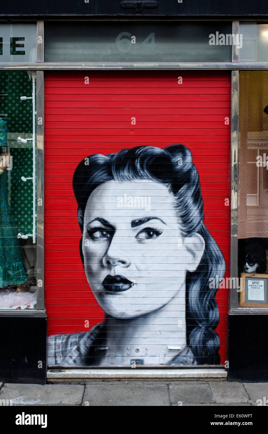 Retro style graffiti on the shutters of a branch of Armstrongs Vintage clothing store in Edinburgh. - Stock Image