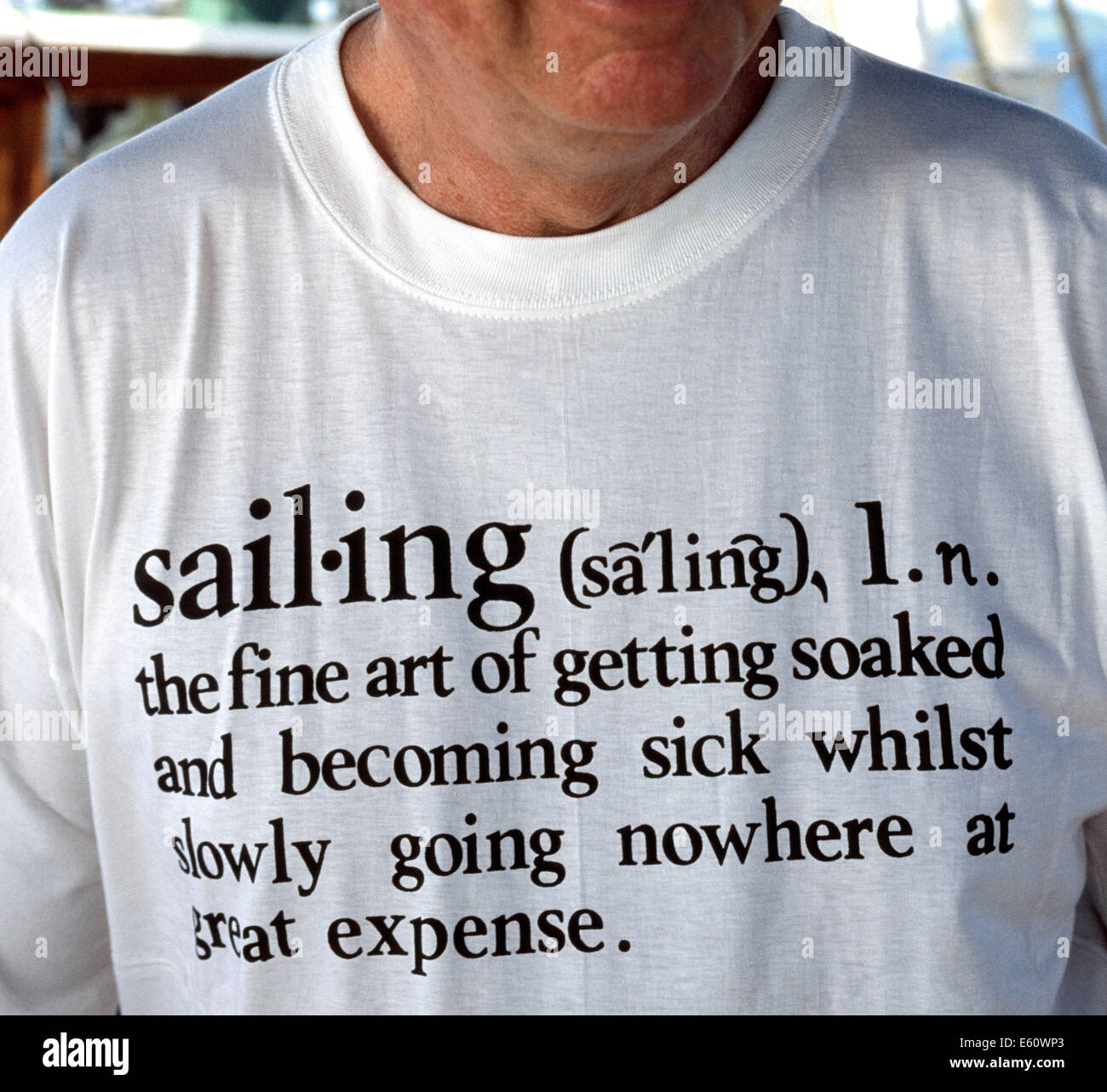 A man aboard a sailboat in the Caribbean Sea wears a white T-shirt with writing that gives a humorous dictionary - Stock Image