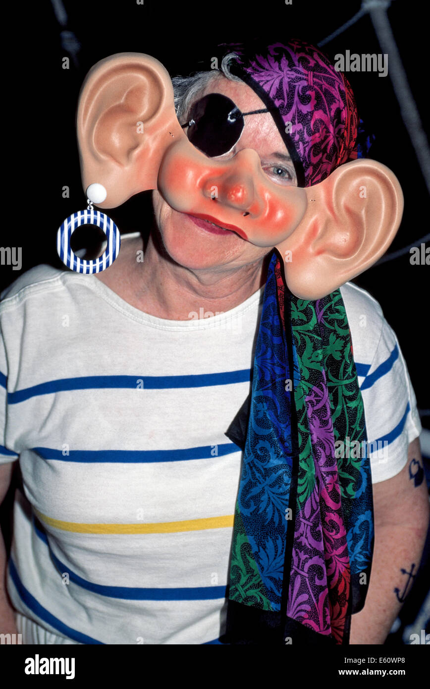 A woman dresses up with a big-eared mask to portray a humorous pirate at a passenger costume party on board a sailing - Stock Image