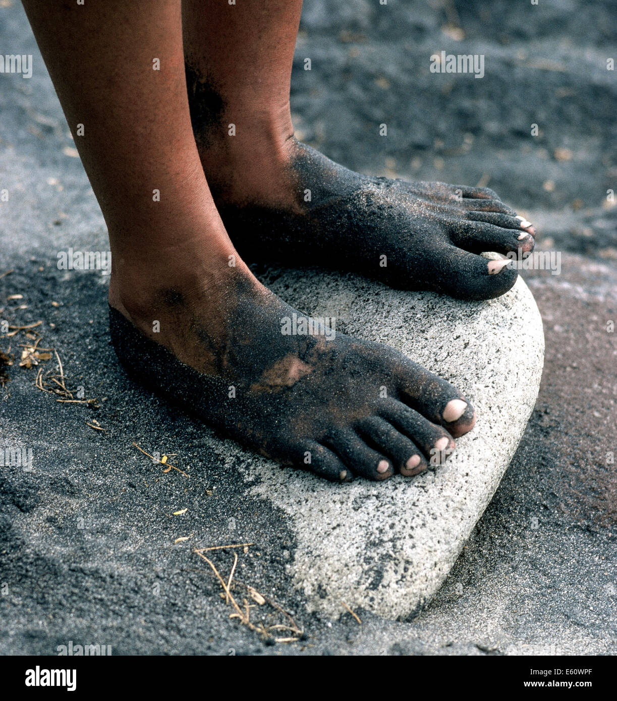 Sticky black sand covers the feet of a beachgoer in Montserrat, a small volcanic island in the Caribbean Sea that - Stock Image