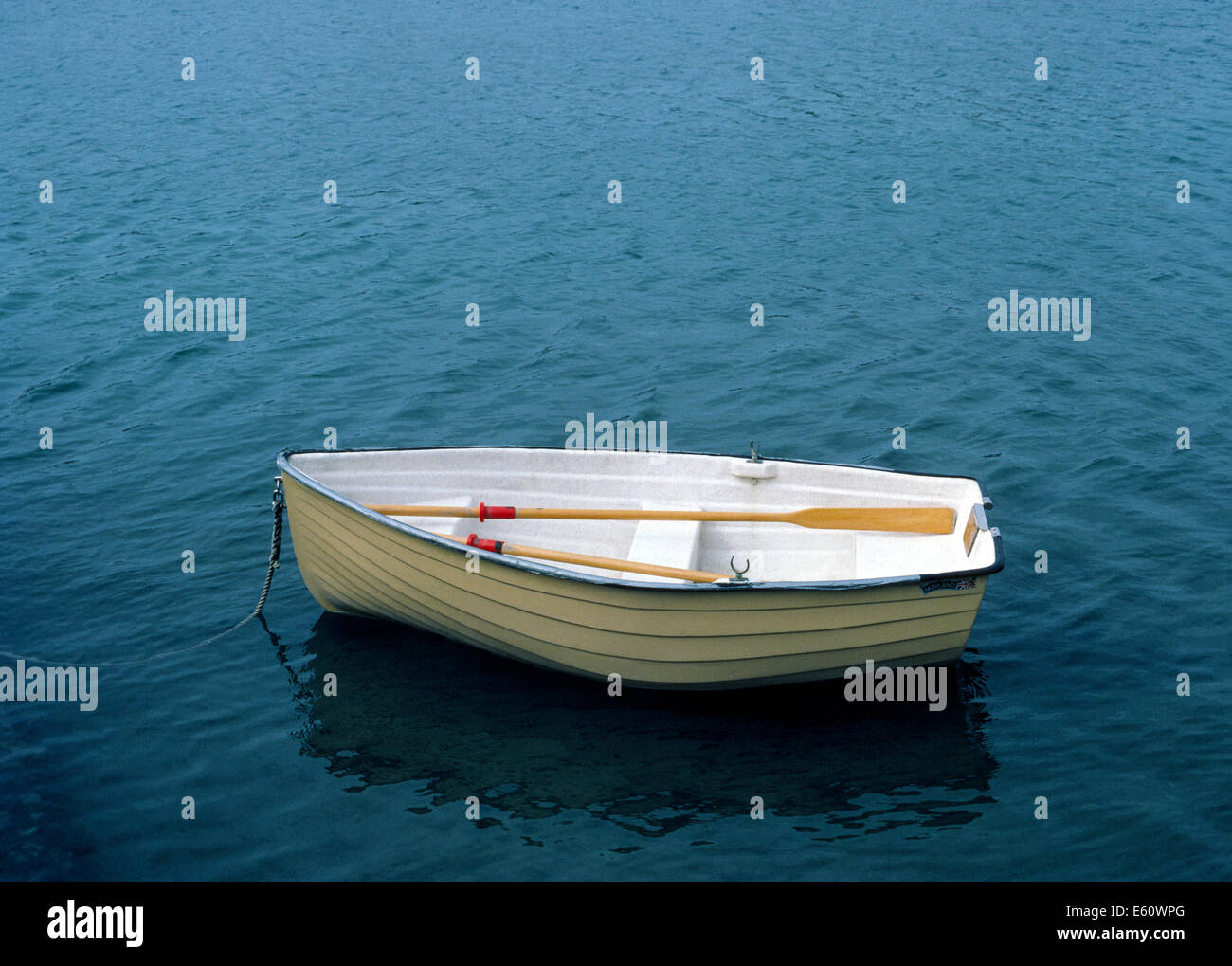 A small dinghy rests in shallow water and waits for its owner to return and use the wooden oars to row back to his - Stock Image