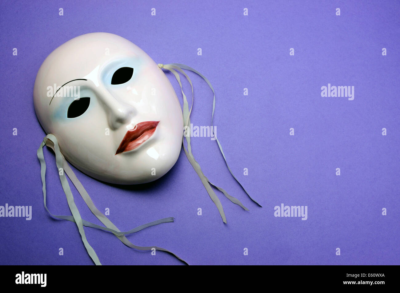 Pale pink ceramic mask on purple background for actor, performance or theater concept with copy space for your text - Stock Image