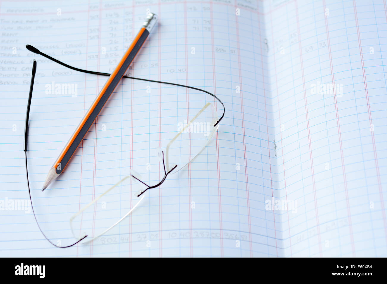 Reading eyeglasses and a pencil on annual Income tax report bookkeeping. Concept photo of tax, taxation, income, - Stock Image
