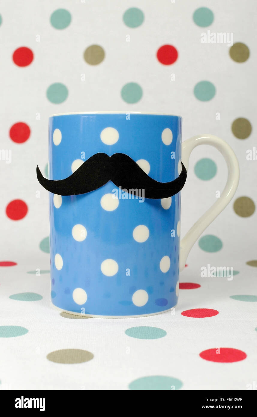 Morning mustache on a blue coffee mug against a polka dot background, for Movember to raise awareness for male health - Stock Image