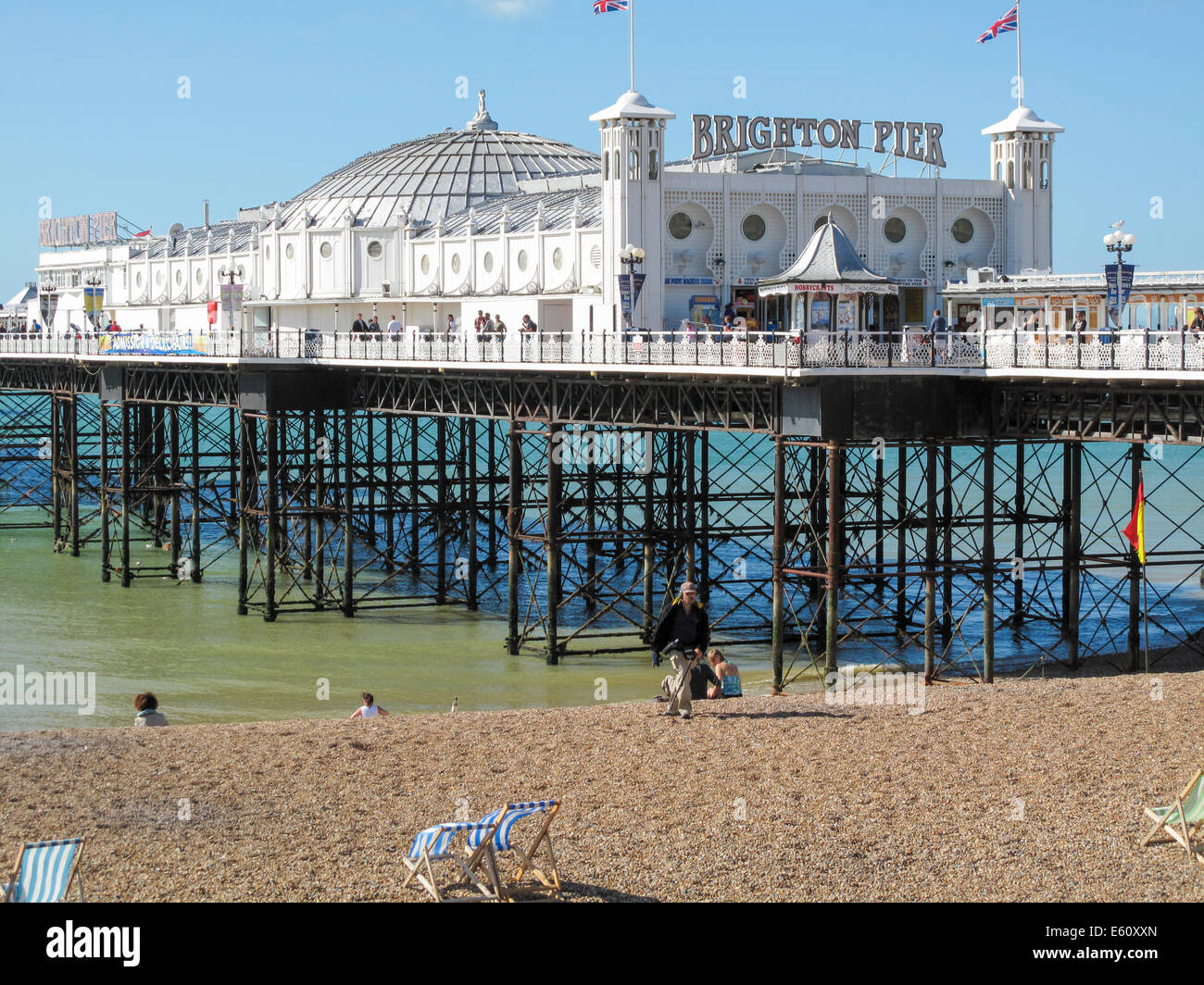 Brighton Pier and Brighton beach on a sunny summer afternoon with a clear blue sky - Stock Image