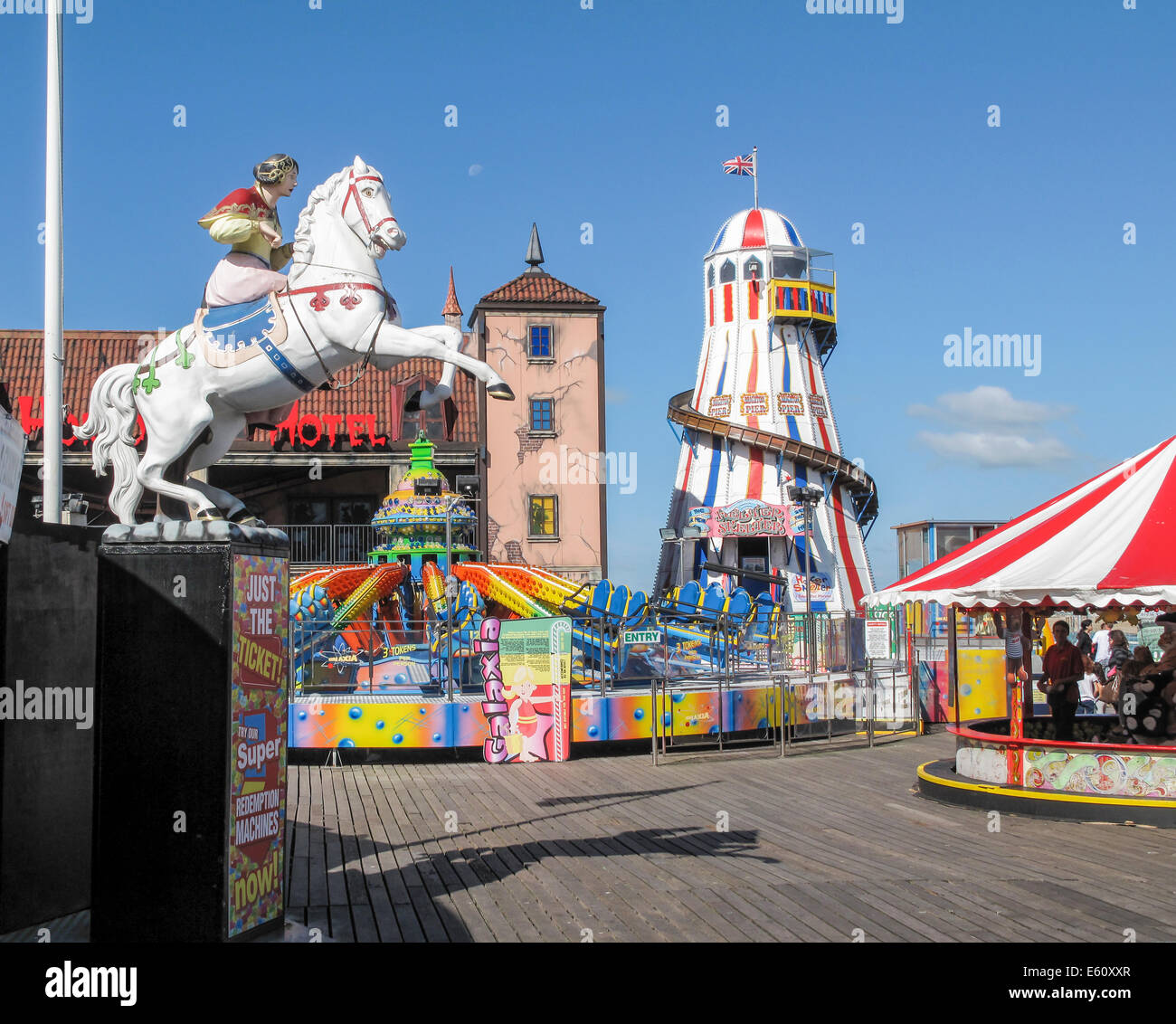 South coast sightseeing: Helter skelter and colourful fairground attractions at the funfair on Brighton Pier popular for family holidays in summer Stock Photo