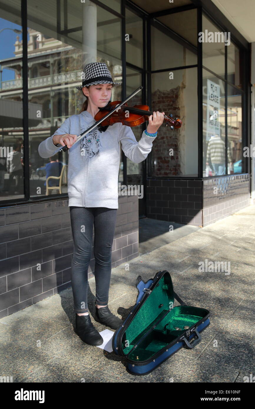 A young girl is busking with her violin in Fremantle, Western Australia. - Stock Image