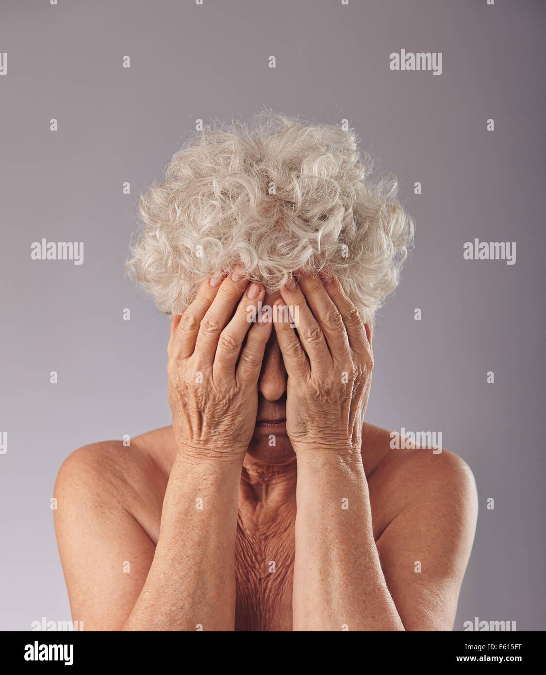 Portrait of  a upset old woman with her head in her hands against grey background. Sad senior woman covering her - Stock Image