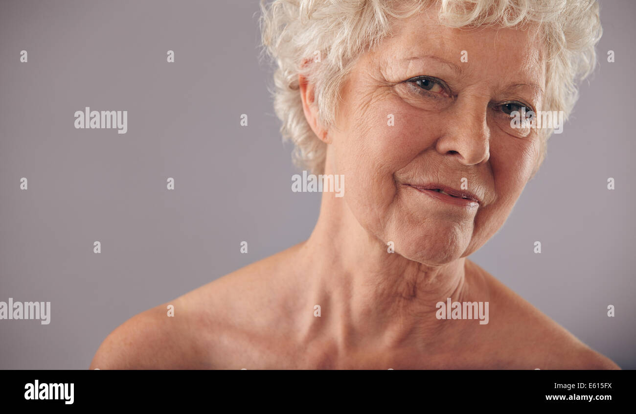 Close-up portrait of old caucasian female face against grey background. Senior woman with wrinkled skin looking - Stock Image