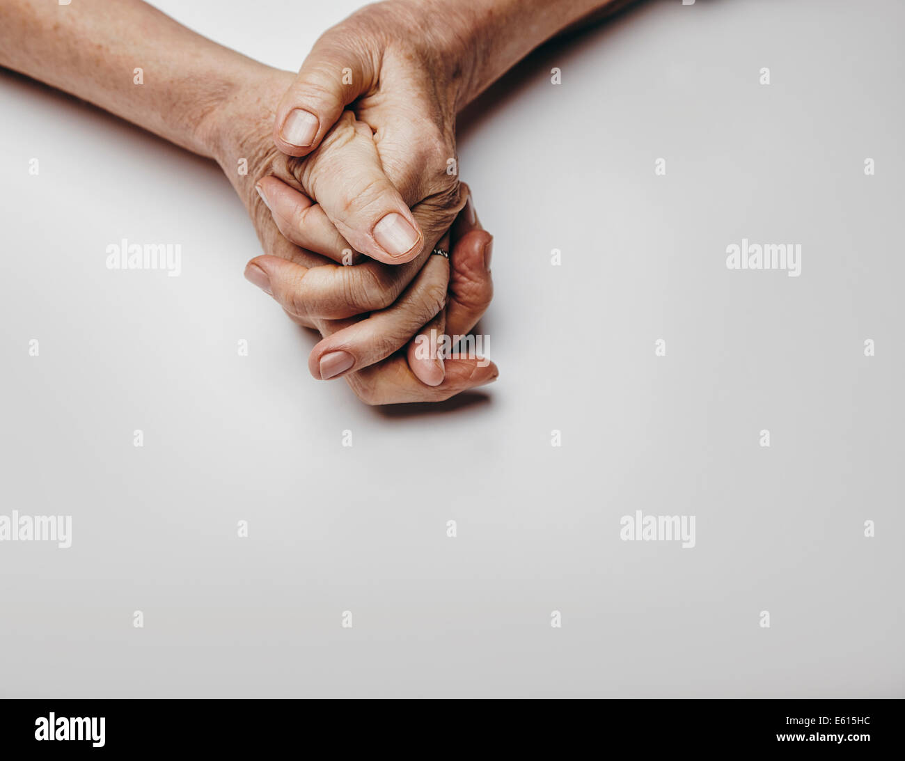 Senior woman's hands isolated on grey background. Hands of a relaxed old female with copy space. Praying hands. - Stock Image