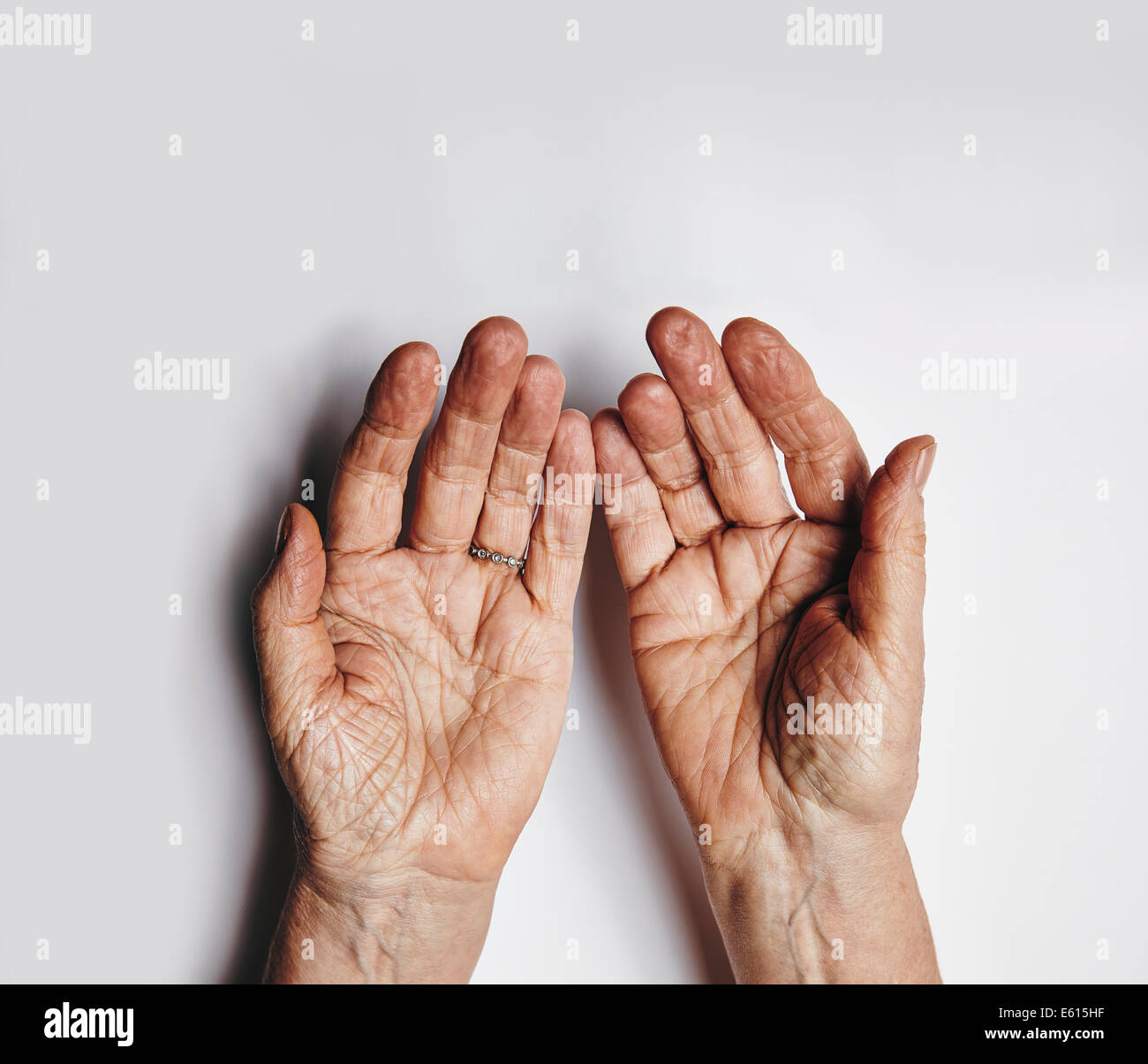 Top view of two empty female hands over grey background. Senior woman hands pleading. Wrinkled palms of aged woman - Stock Image
