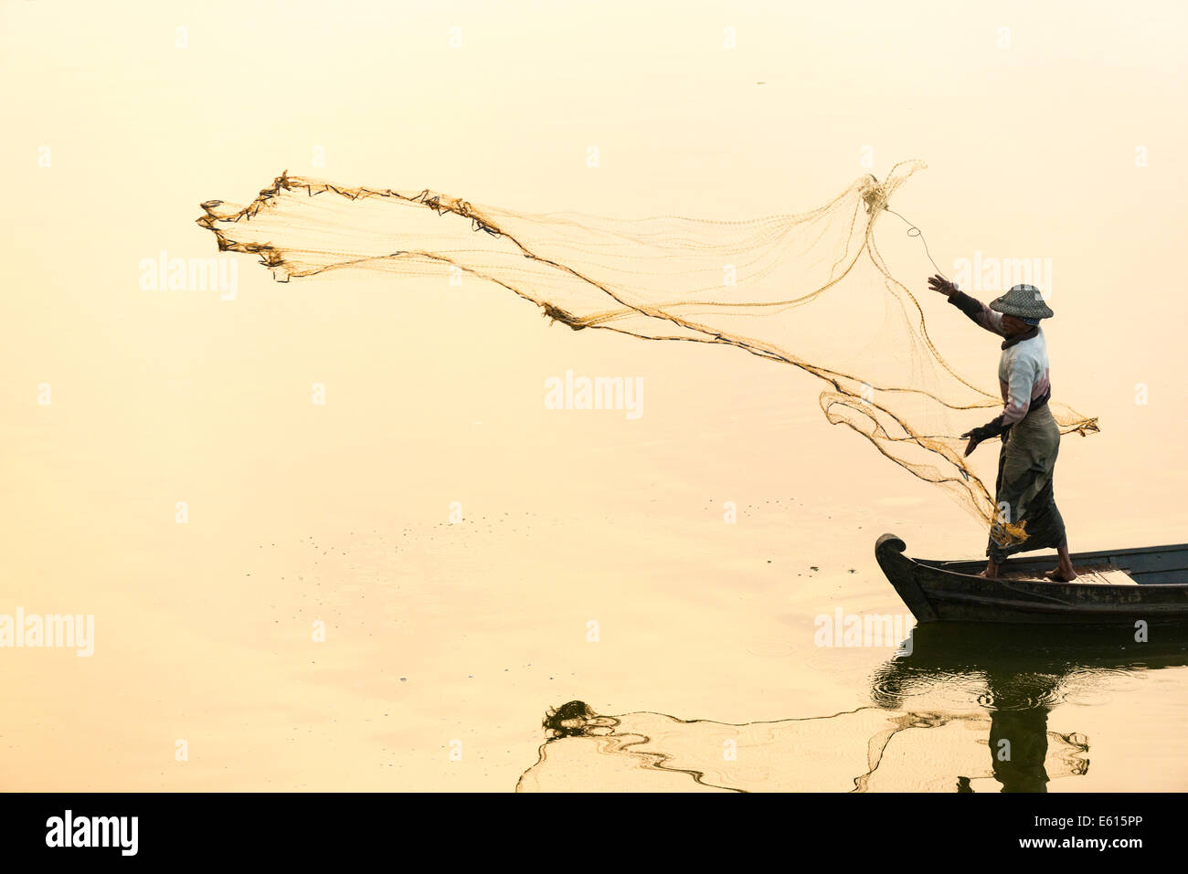 Fisherman in a boat tossing out a net, morning light, Thaungthaman Lake, Amarapura, Mandalay Division, Myanmar - Stock Image