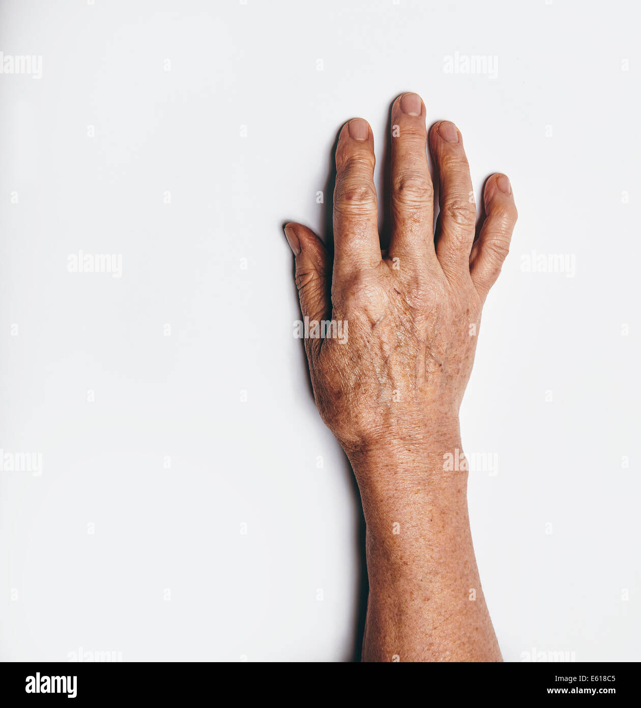 One hand of an elderly woman isolated on white background. Senior lady wrinkled hand with copyspace for your text. - Stock Image