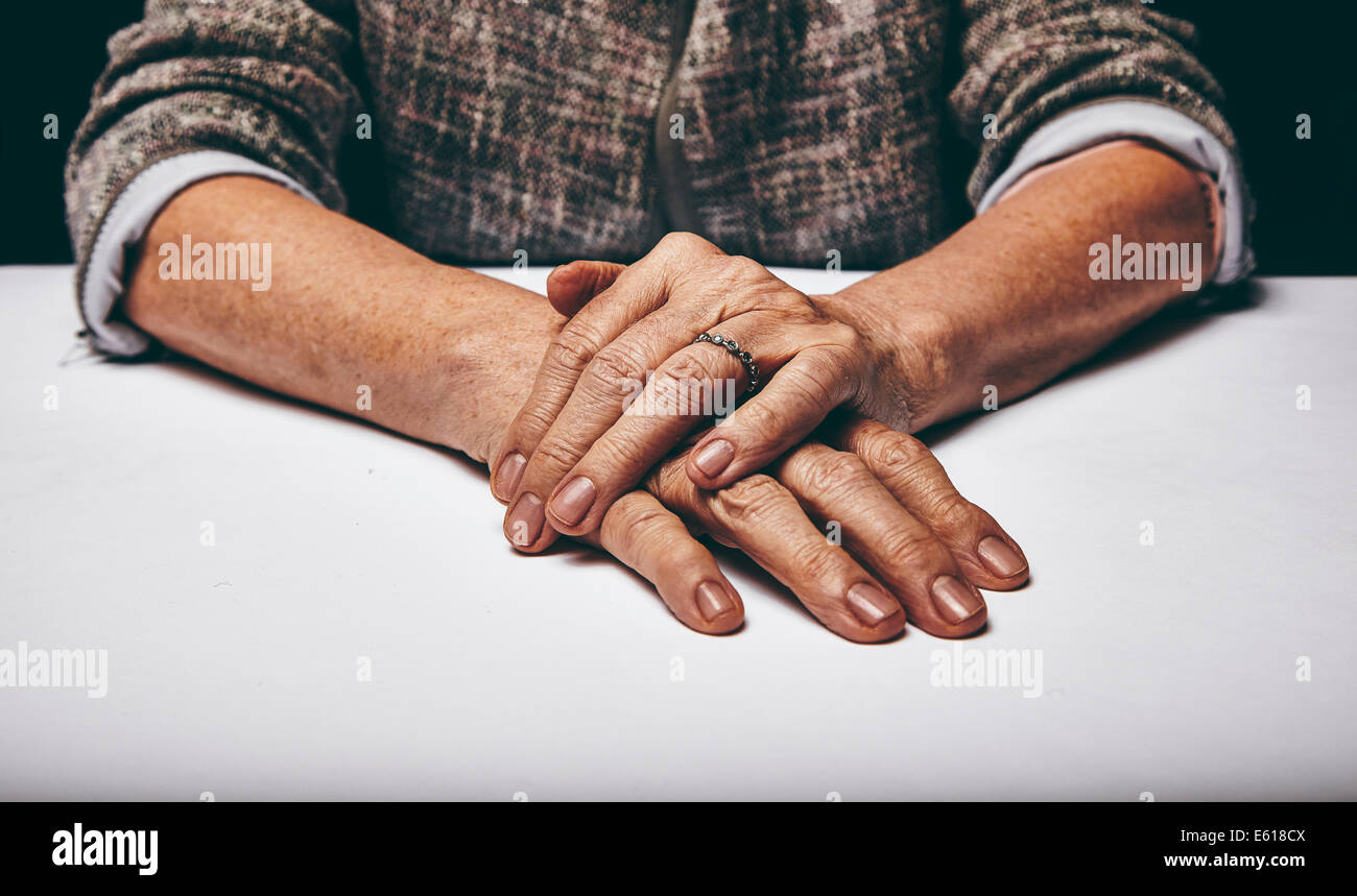 Close-up studio shot of a senior woman's hands resting on grey surface. Old lady sitting with her hands clasped - Stock Image