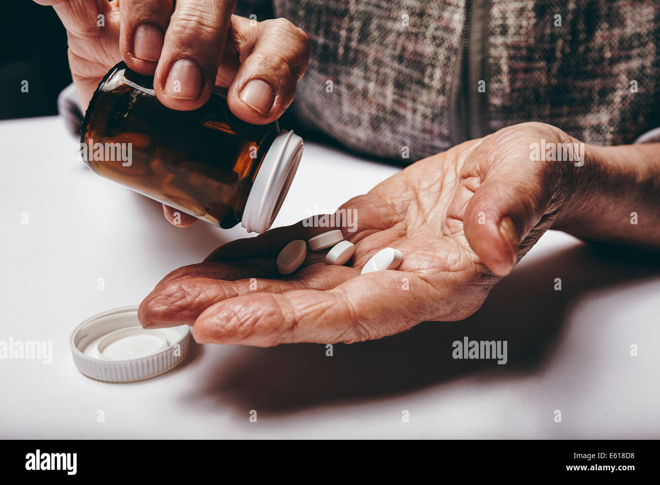 Close-up image of senior woman taking out pills from the pills bottle. Focus on hands. Old female taking medicines. - Stock Image