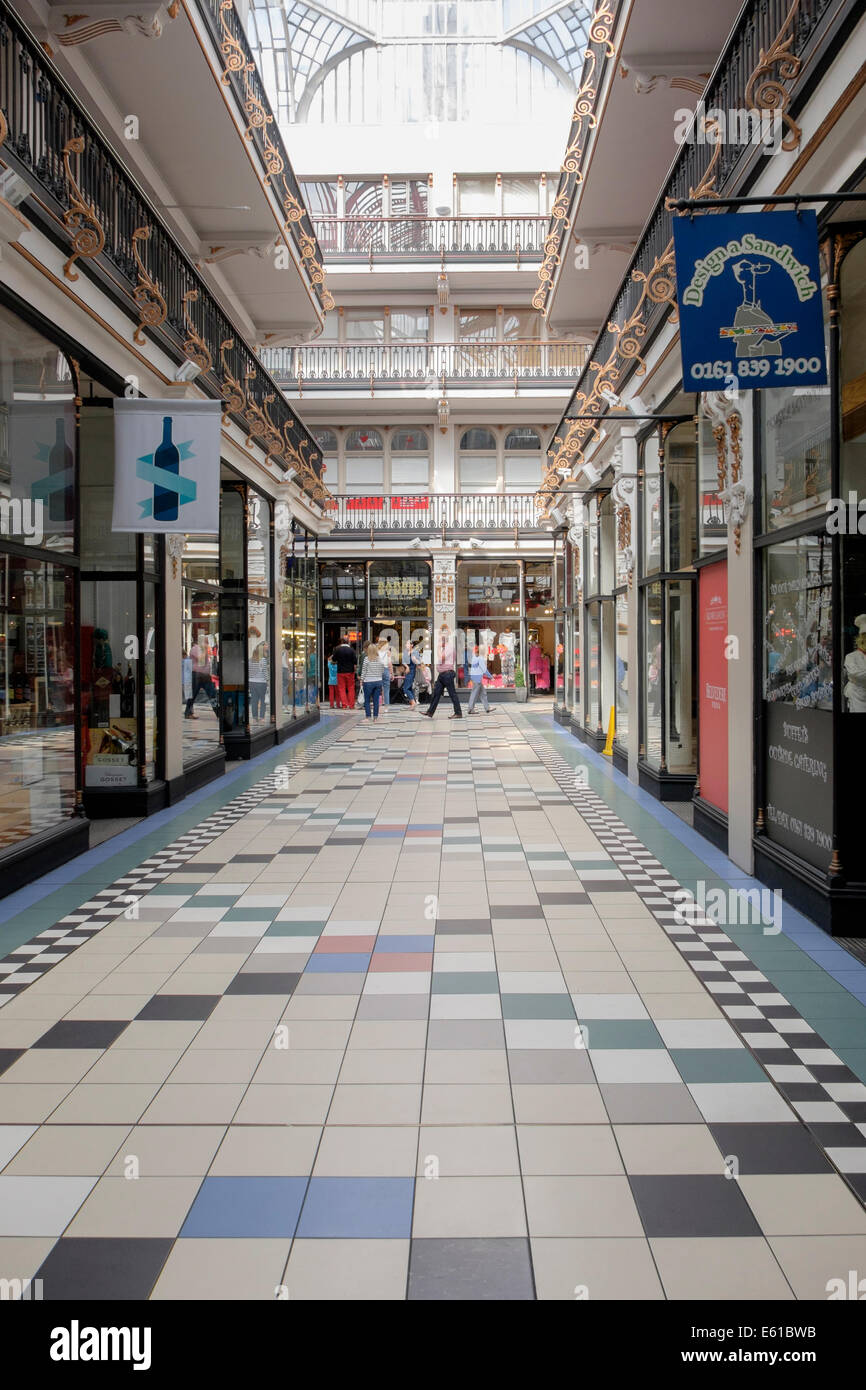 Street scene inside Victorian shopping arcade covered by a glass roof. Barton Arcade, Deansgate, Manchester, England, - Stock Image
