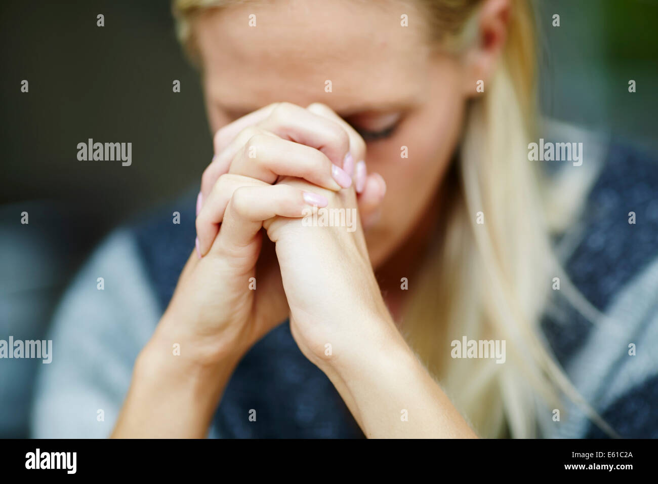 Woman with clasped hands - Stock Image