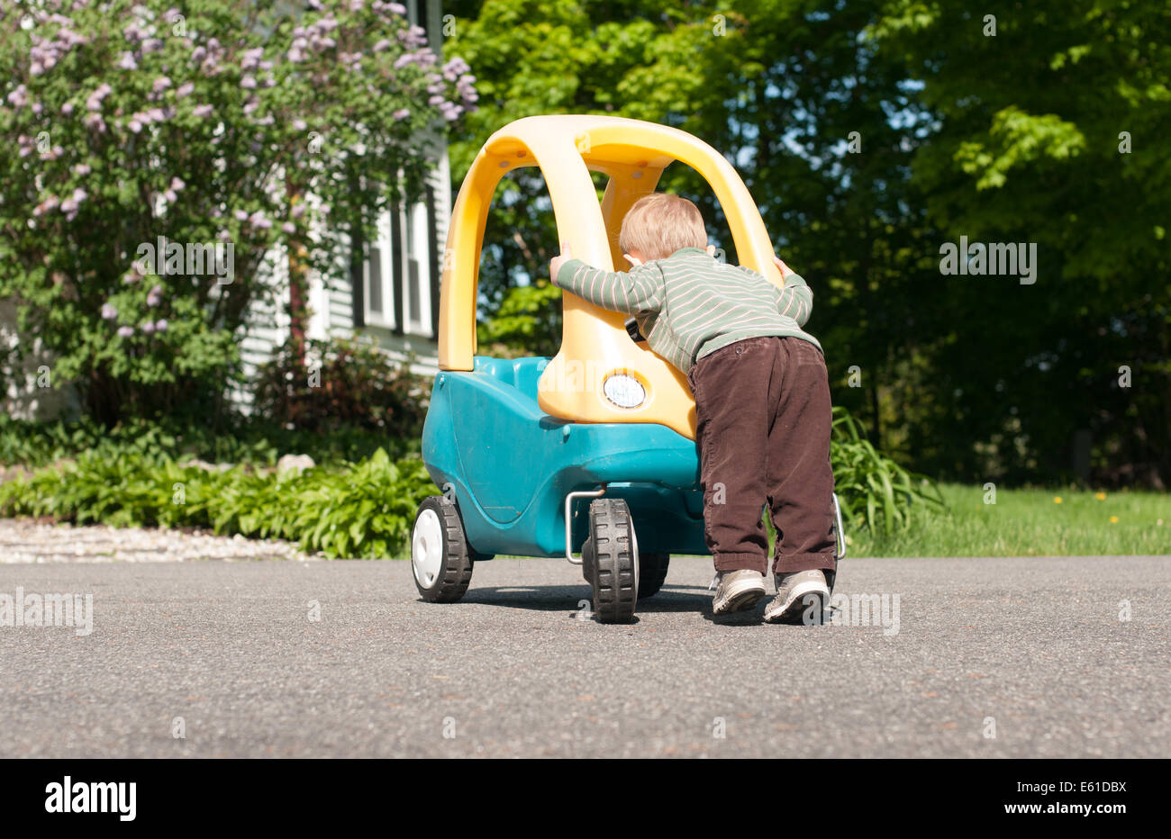 A toddler boy leans over the front of his large toy car as if he is working on it. - Stock Image