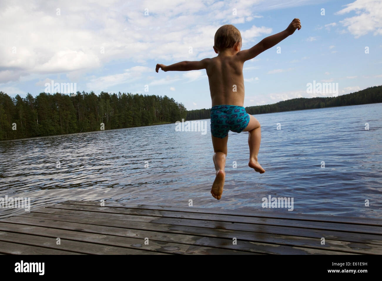 A boy jumping into water off the pier in summer in Finland - Stock Image