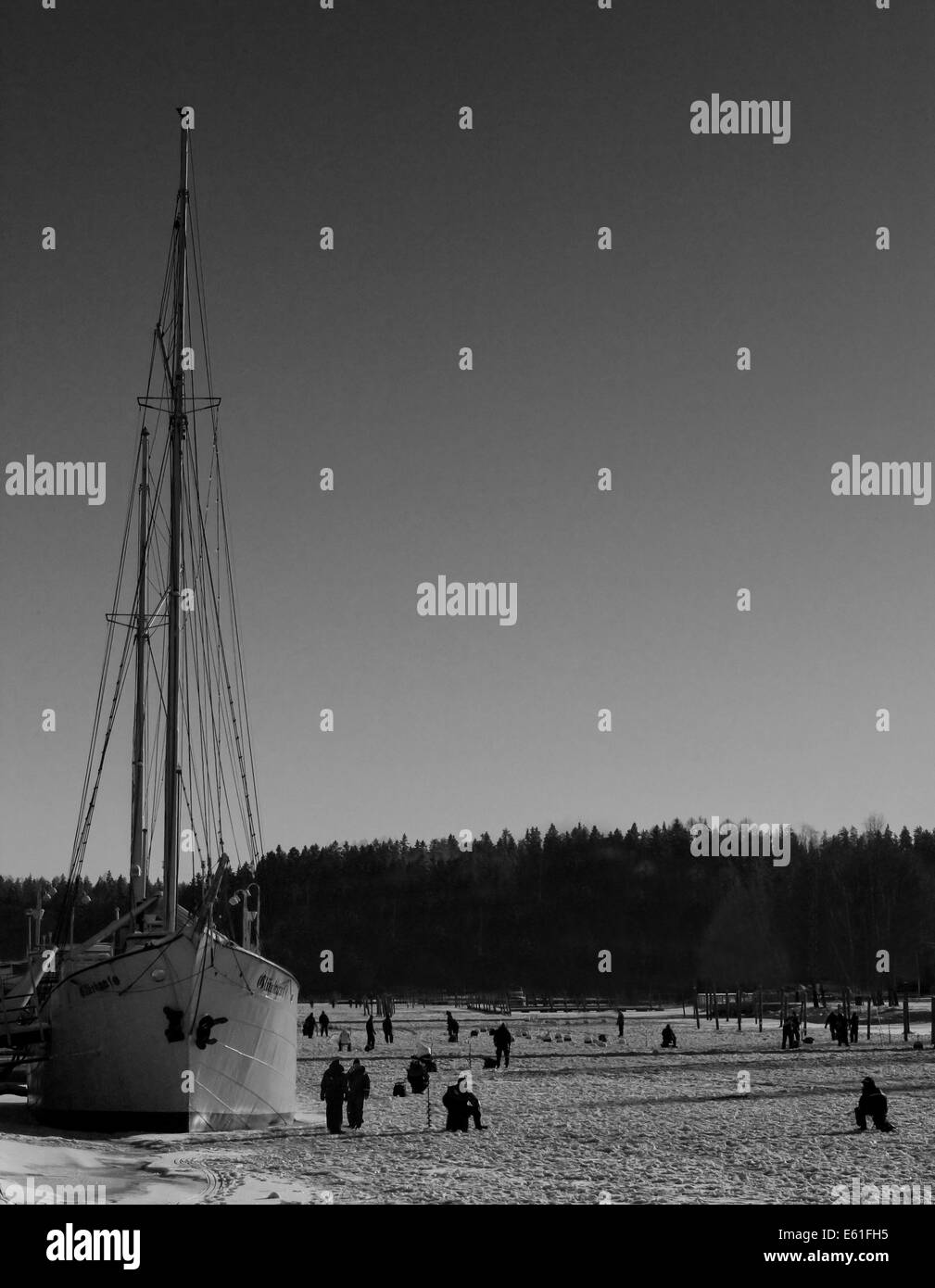 An image of Porvoo river in Finland and a tall ship moored with thick ice covering the river and fishermen on the Stock Photo