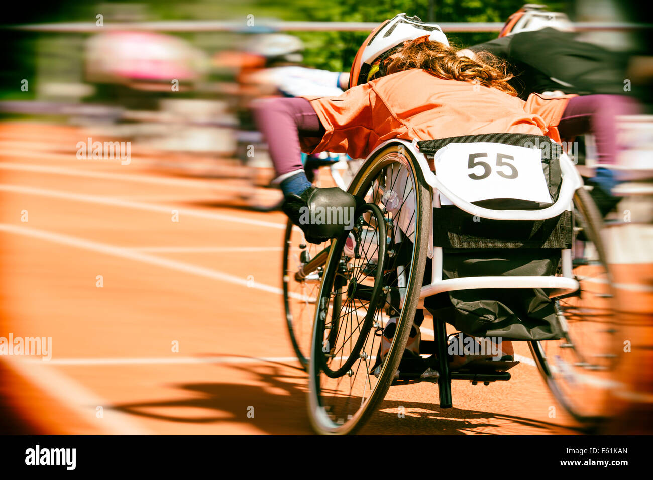 Athletes  at a wheelchair race in a stadium with motion blur, lens vignetting and  Nik collection Analog Efex Pro - Stock Image