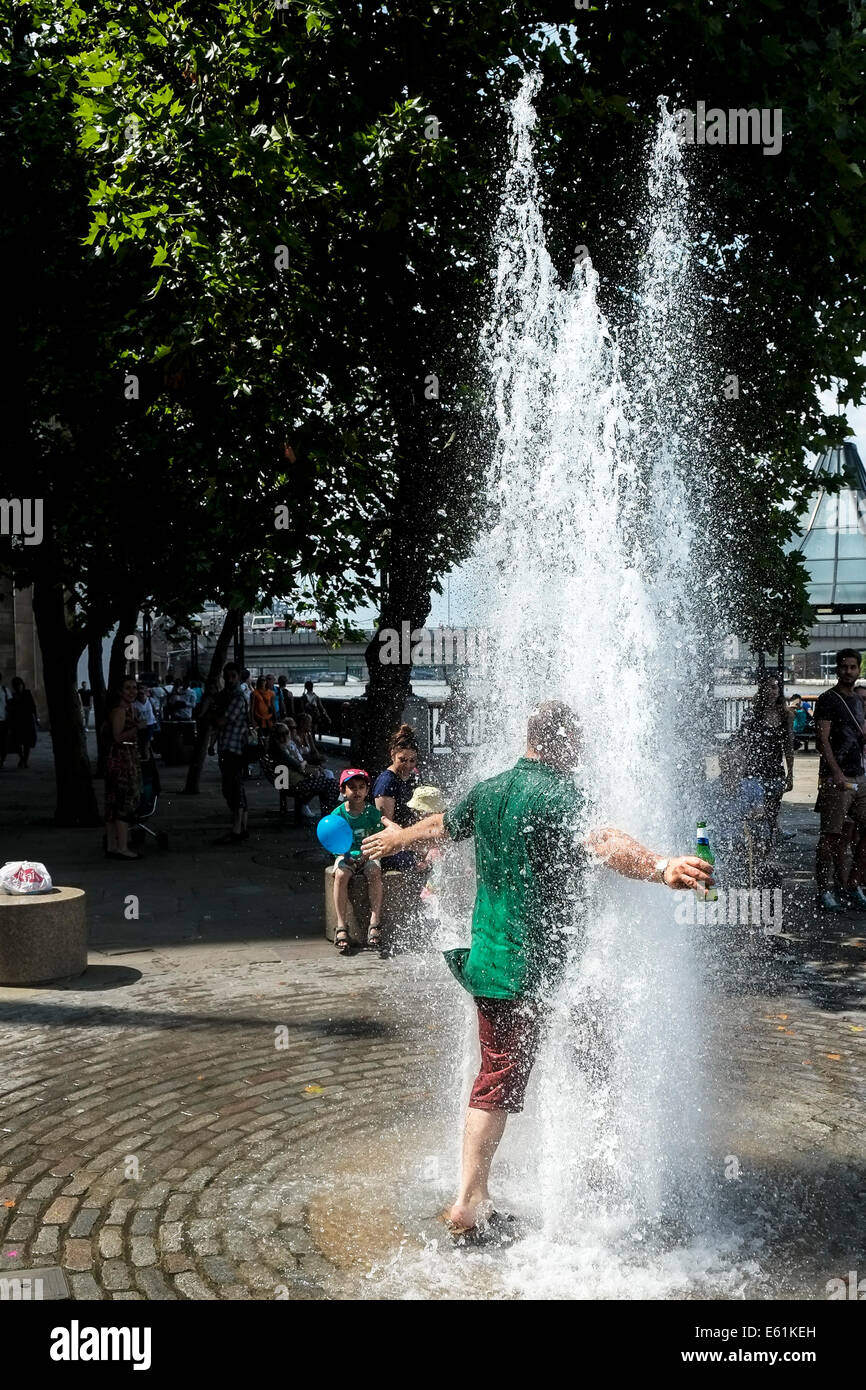 A man carrying a bottle of beer runs into a fountain of water to escape the hot weather in London. - Stock Image