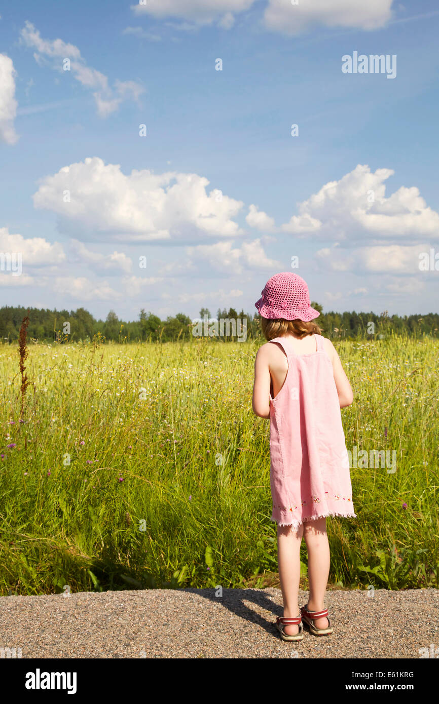 Girl with pink dress and pink summer hat standing at the edge of a cornfield looking at the field - Stock Image
