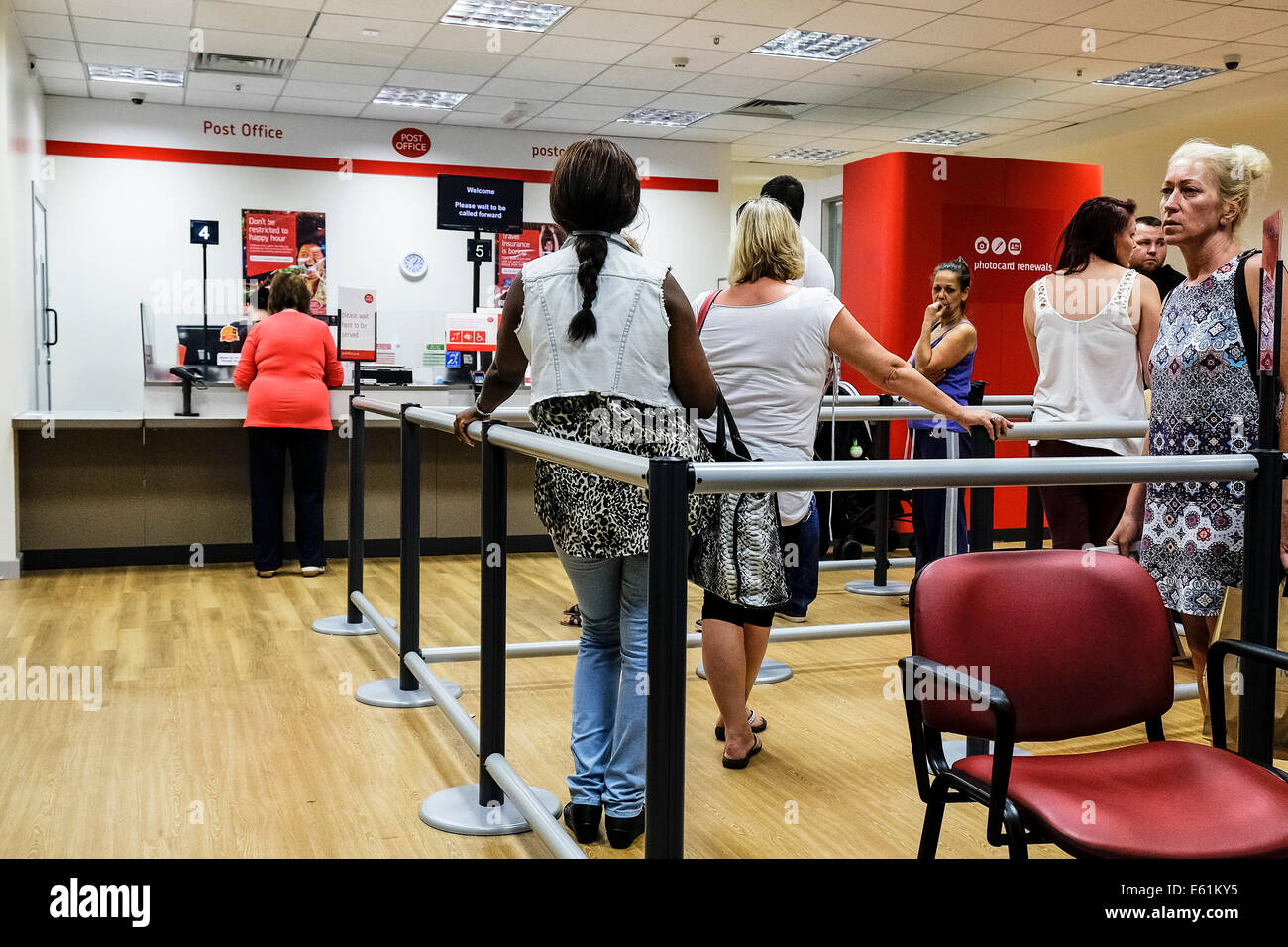 Patient customers queueing in a post office. Stock Photo
