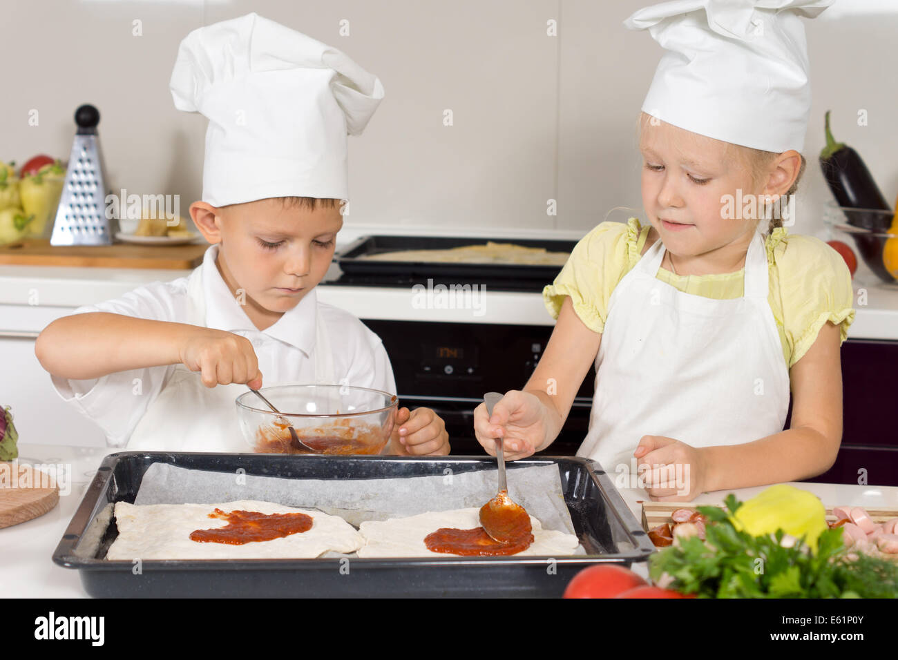 Two young children wearing chefs uniforms making themselves a homemade pizza spreading the tomato paste onto the - Stock Image
