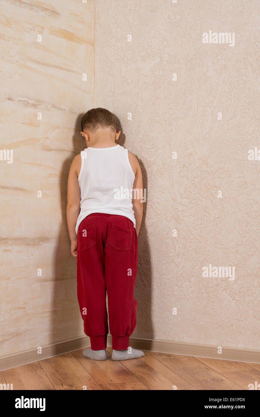 White Little Boy Facing Wooden Walls. Very Shy Looking at Camera - Stock Image