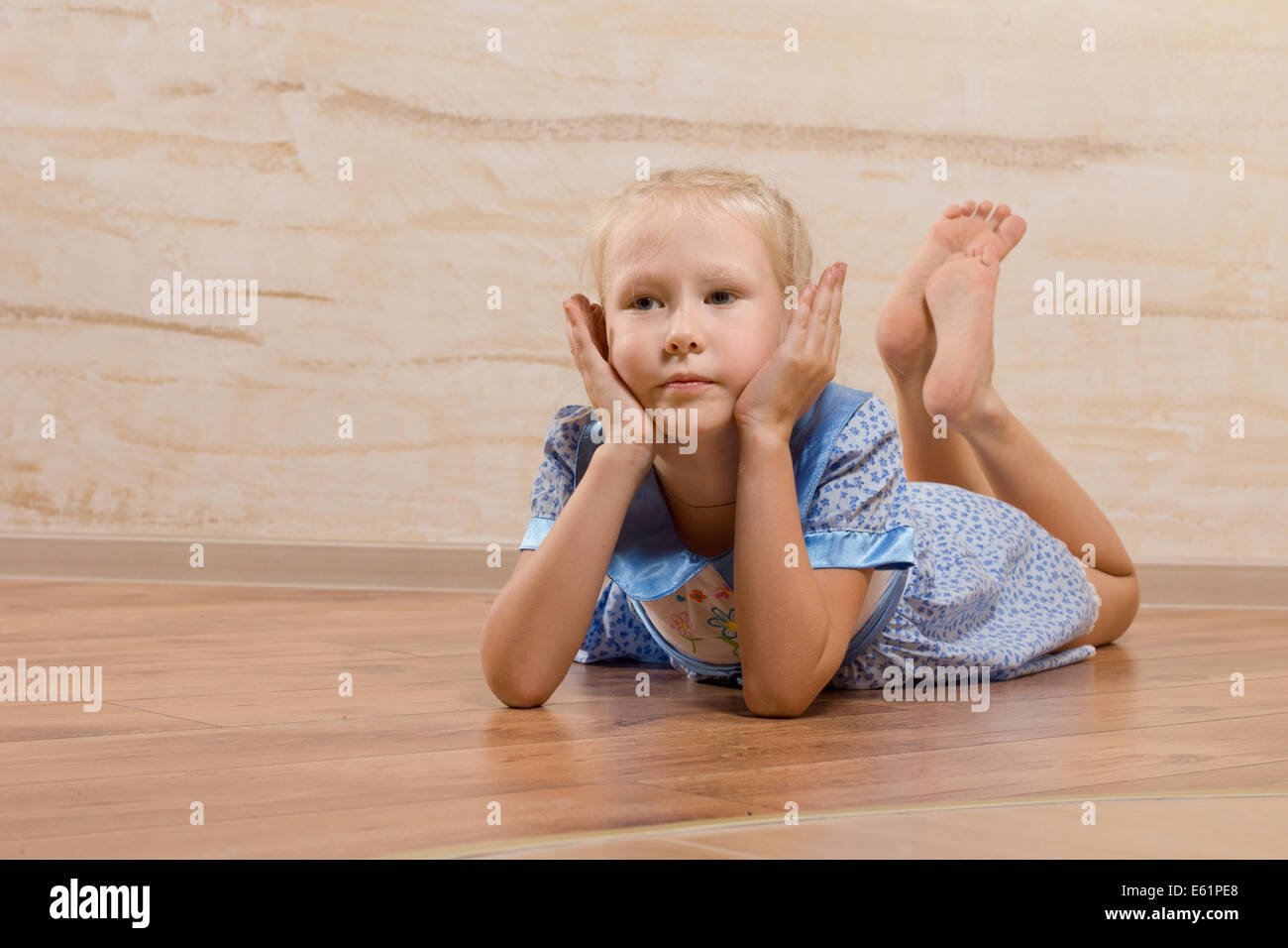 little girl lying Bored little girl lying on the wooden floor with her bare feet up in the  air and her chin resting on her hands as she stares ahe