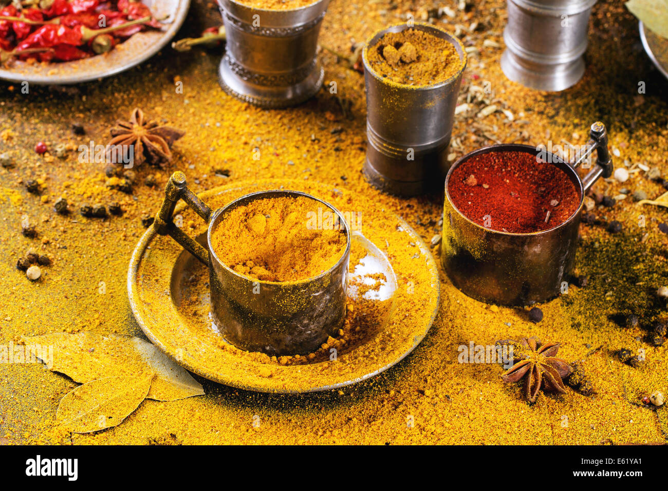 Set of spices pepper, turmeric, anise, coriander in vintage metal cups over yellow curry powder Stock Photo