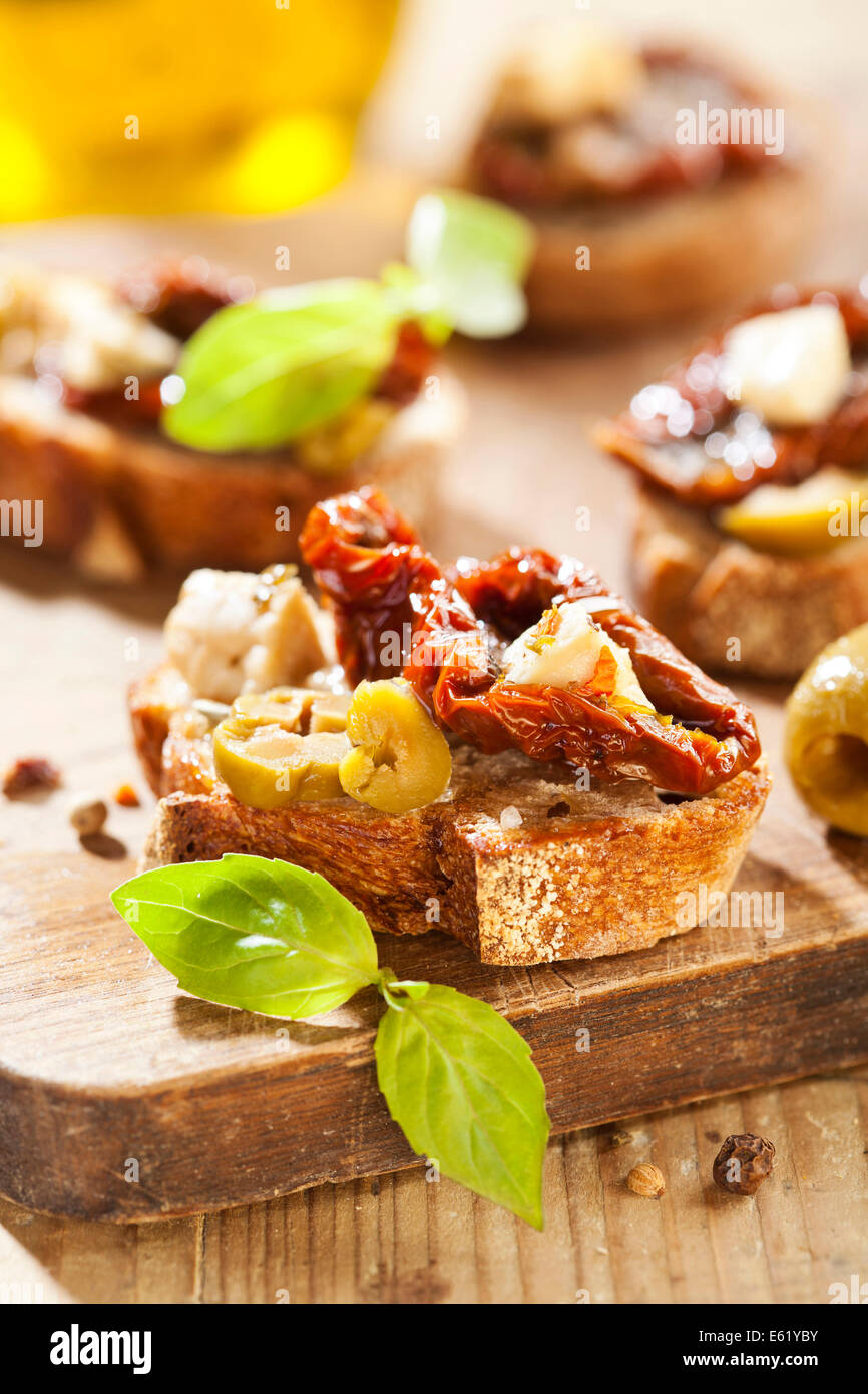 Italian appetizer bruschetta with olive oil, olives, sun-dried tomatoes and cheese. - Stock Image