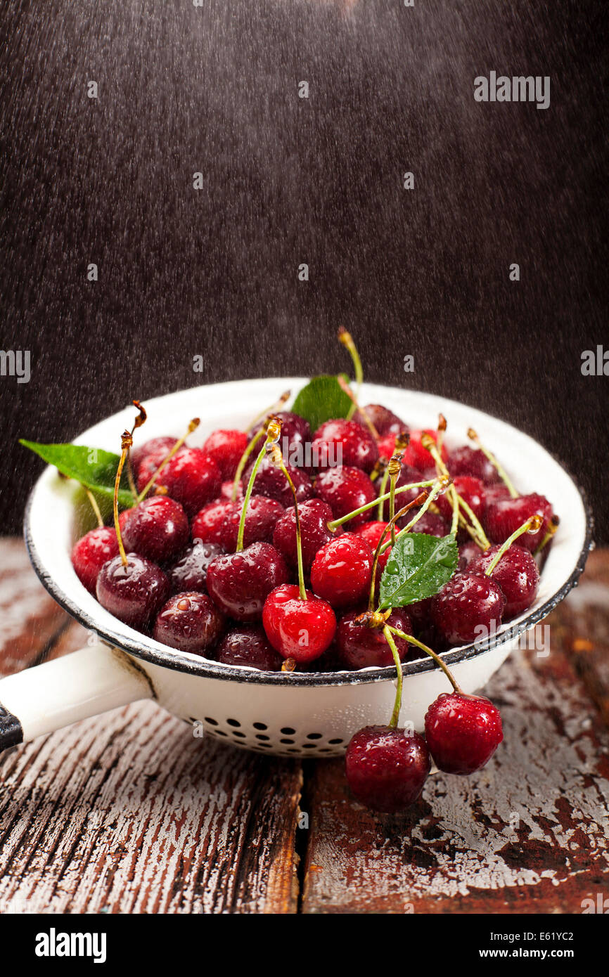 Fresh red cherries being washed in colander. - Stock Image