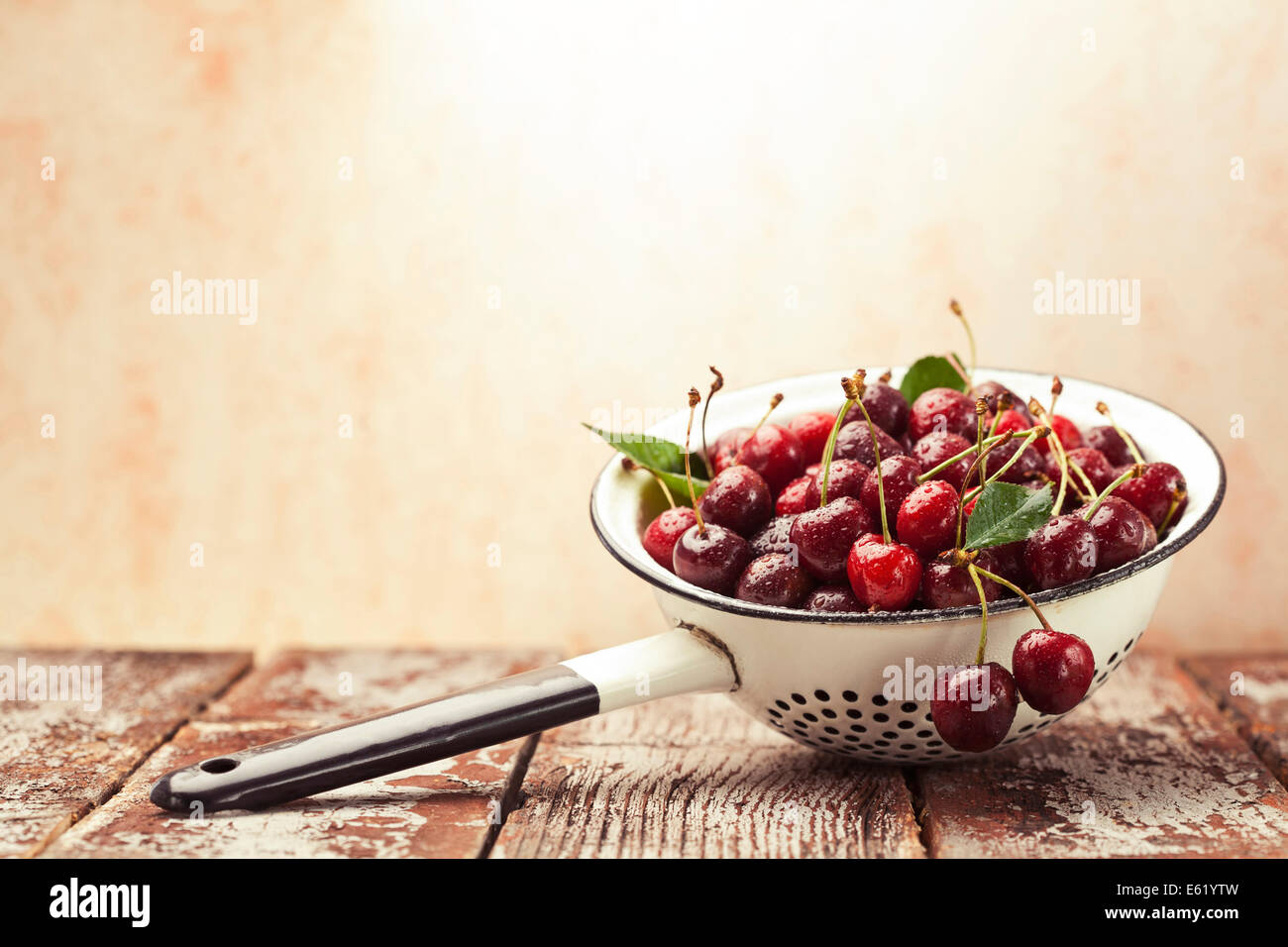 Ripe cherries in vintage colander on wooden rustic background - Stock Image