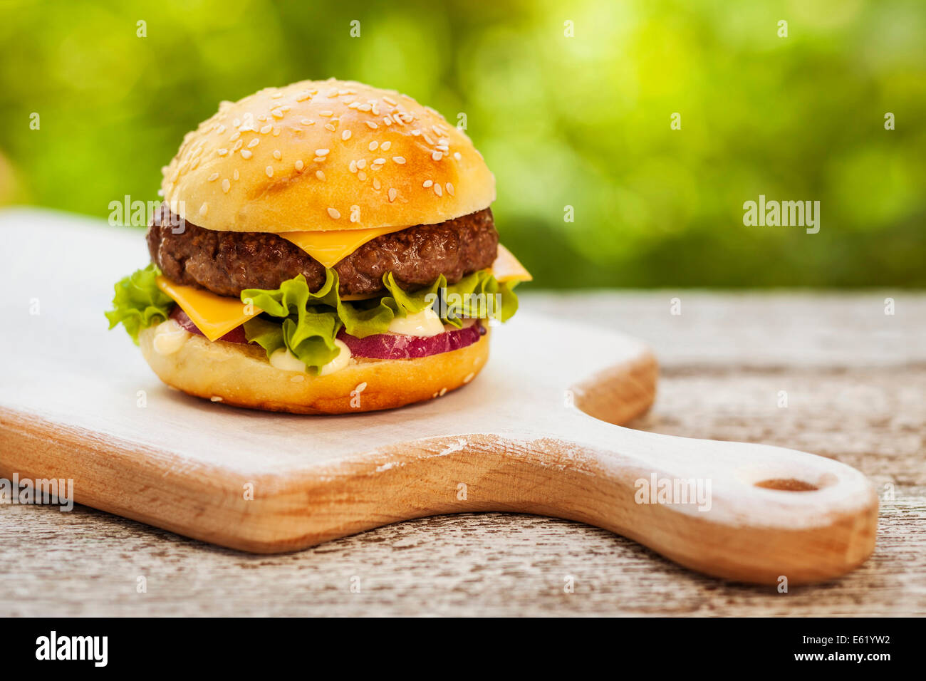 Tasty burger with cheese, lettuce, onion and tomatoes served outdoor on a wooden table - Stock Image