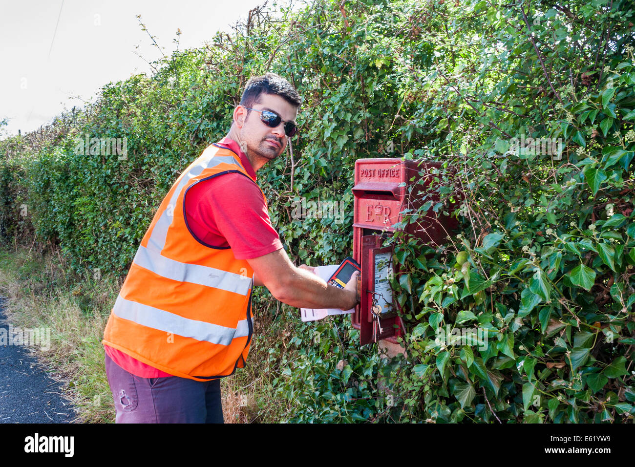 Royal Mail postman collects mail from rural pillar box - Stock Image